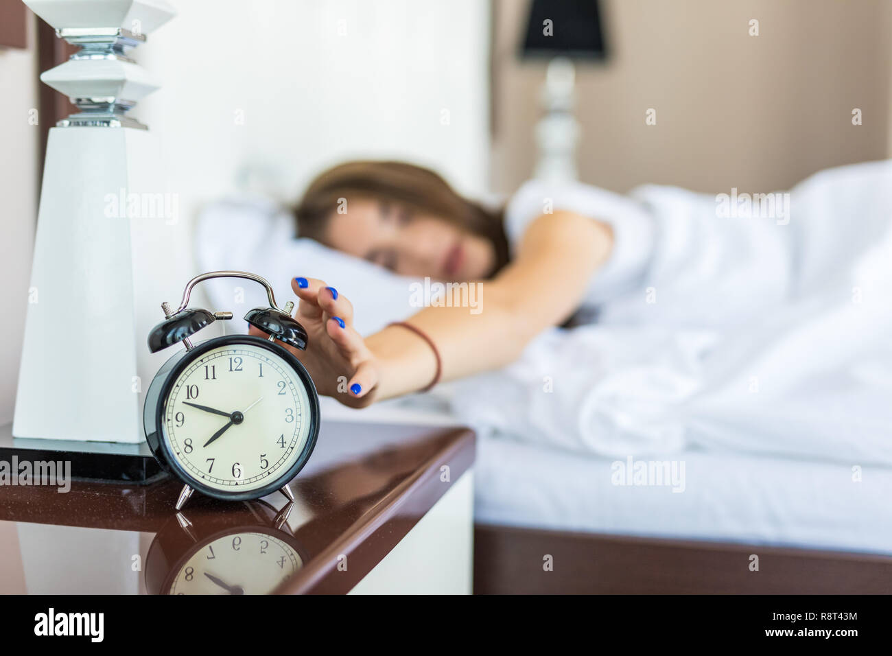 Young Woman Turn Off Alarm Clock In Good Morning Wake Up For Sleep With Closeup Foreground Alarm Clock Relax And Lifestyle Concept