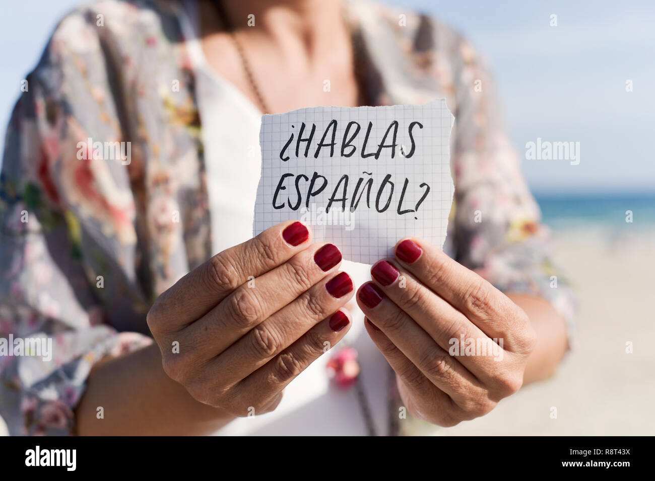 closeup of a caucasian woman outdoors showing a piece of paper with the question hablas espanol, do you speak spanish written in spanish - Stock Image