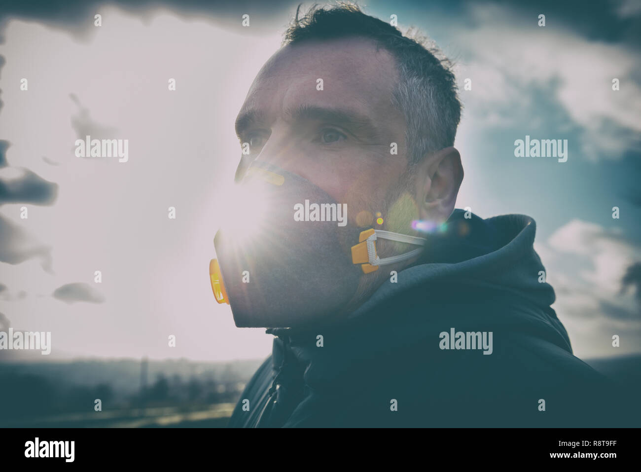 man wearing a real anti-pollution, anti-smog and viruses face mask; dense smog in air - Stock Image