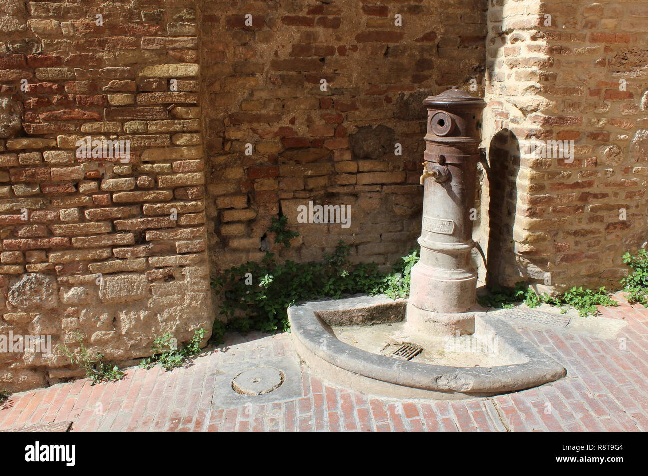 Drinking fountain in front of a very old wall in San Gimignano, Italy Stock Photo