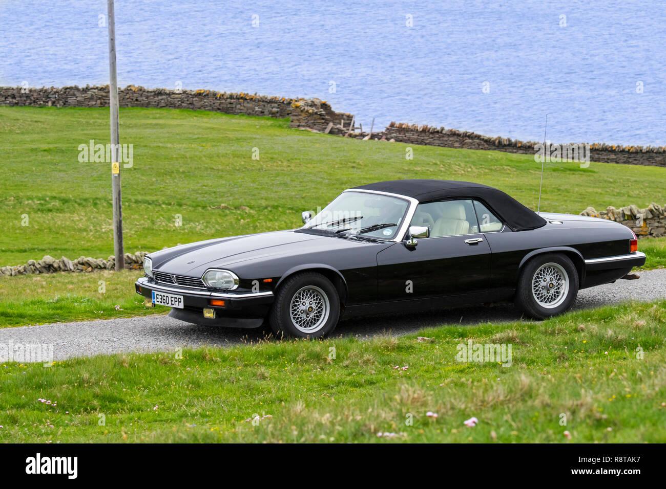 Black 1988 Jaguar XJ-S V12 convertible classic sports car driving along coastal road - Stock Image