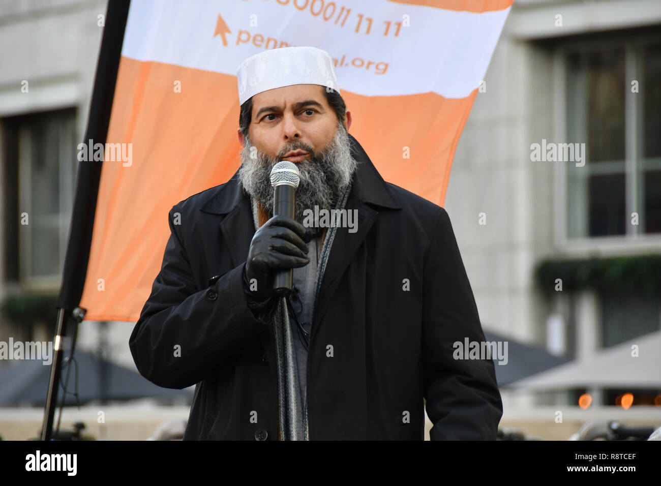 """London, UK. 17th Dec, 2018. Speaker Shaykh Ibrahim Mogra at Penny Appeal Team Orange unveiling 5 life-size ice statues """"What Would Jesus Do?"""", symbolising homeless families to promote their winter campaign. The frozen family will depict the plight of the 140* families who become homeless everyday, and the 900* children who become homeless every month on 17th December at Canary Wharf, London, UK. Credit: Picture Capital/Alamy Live News - Stock Image"""