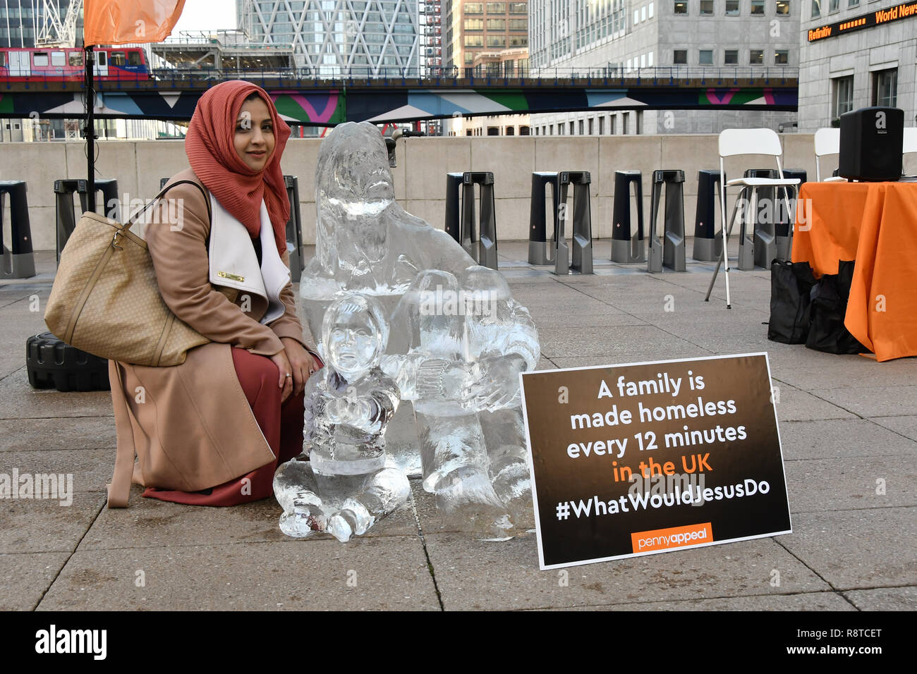 """London, UK. 17th Dec, 2018. Sabia Kamali of Islam Channel at Penny Appeal Team Orange unveiling 5 life-size ice statues """"What Would Jesus Do?"""", symbolising homeless families to promote their winter campaign. The frozen family will depict the plight of the 140* families who become homeless everyday, and the 900* children who become homeless every month on 17th December at Canary Wharf, London, UK. Credit: Picture Capital/Alamy Live News - Stock Image"""