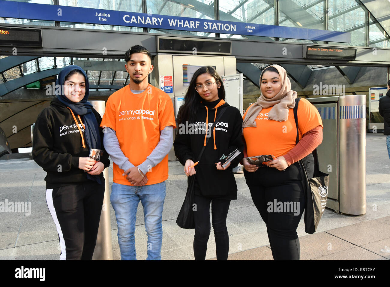 """London, UK. 17th Dec, 2018. Penny Appeal Team Orange unveiling 5 life-size ice statues """"What Would Jesus Do?"""", symbolising homeless families to promote their winter campaign. The frozen family will depict the plight of the 140* families who become homeless everyday, and the 900* children who become homeless every month on 17th December at Canary Wharf, London, UK. Credit: Picture Capital/Alamy Live News - Stock Image"""
