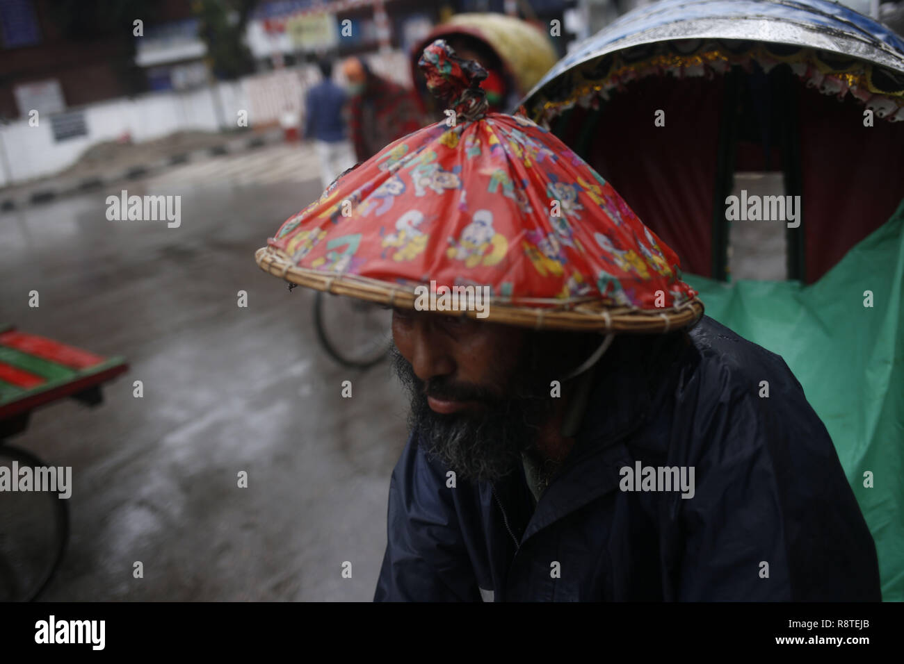 "December 17, 2018 - Dhaka, Bangladesh - A Rickshaw puller waits for passenger during rain near Polashi. According to news, part of the country experienced light to moderate rain due to the cyclonic storm, ""Phethaiâ (Credit Image: © MD Mehedi Hasan/ZUMA Wire) - Stock Image"
