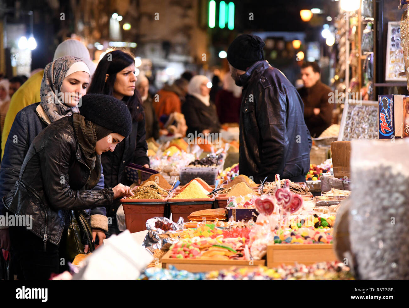 Damascus, Syria. 17th Dec, 2018. Syrian women shop at a marketplace in the old city of Damascus, capital of Syria, on Dec. 17, 2018. As Christmas and the New Year approach, Syrians in Damascus shopped for gifts, candies and decorations at marketplaces. Credit: Ammar Safarjalani/Xinhua/Alamy Live News - Stock Image
