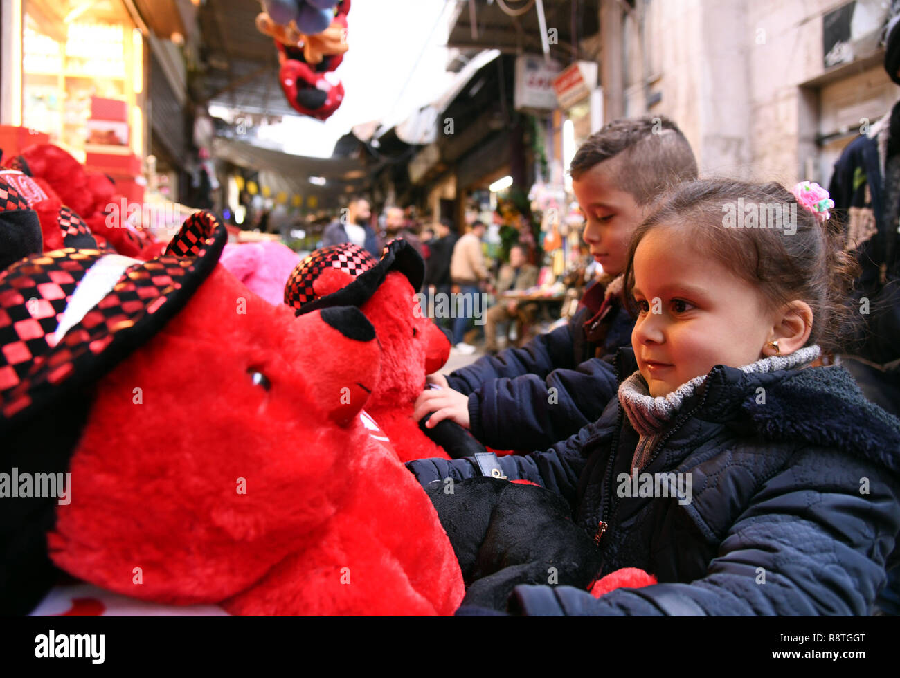 Damascus, Syria. 17th Dec, 2018. Syrian children look at toy bears at a marketplace in the old city of Damascus, capital of Syria, on Dec. 17, 2018. As Christmas and the New Year approach, Syrians in Damascus shopped for gifts, candies and decorations at marketplaces. Credit: Ammar Safarjalani/Xinhua/Alamy Live News - Stock Image