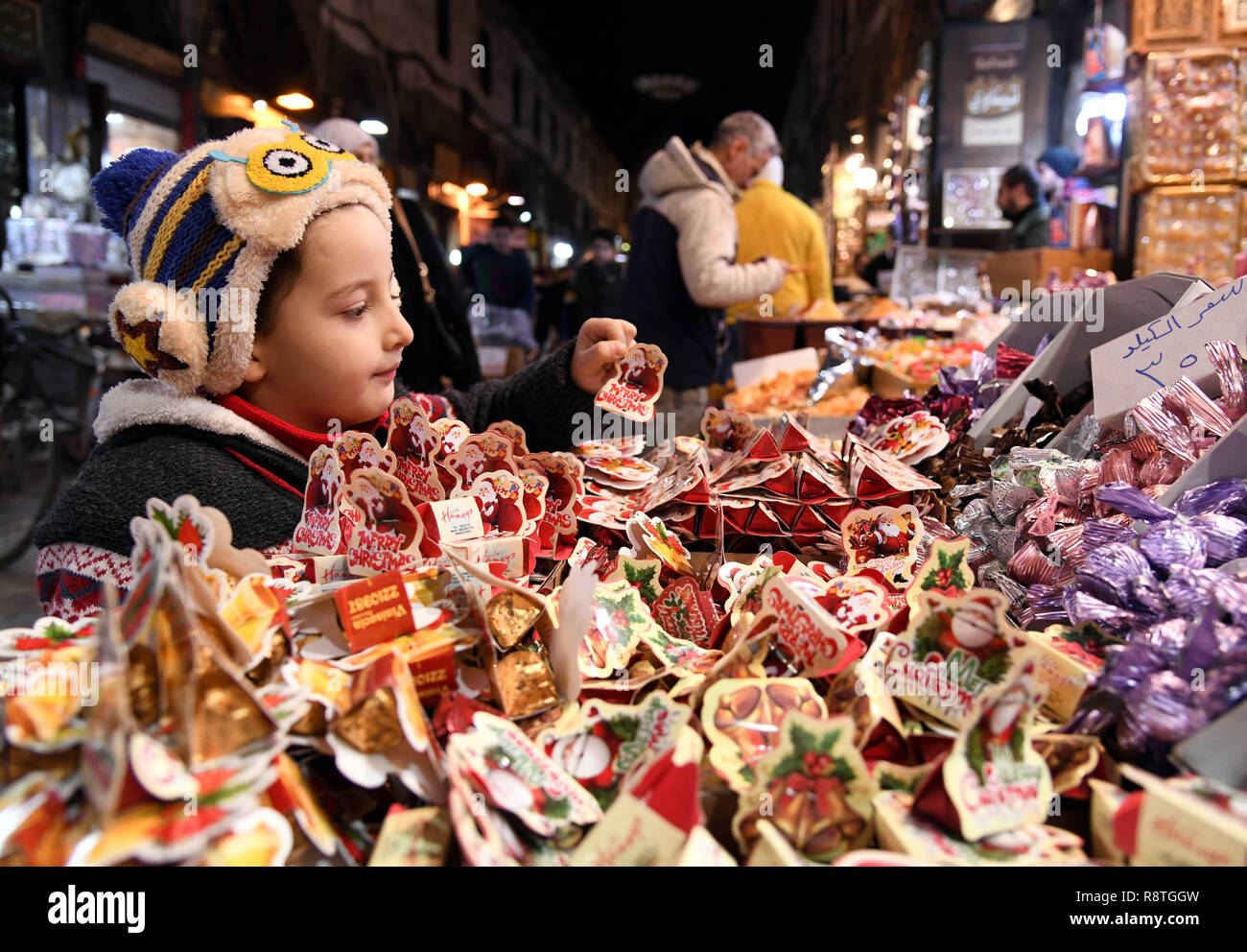 Damascus, Syria. 17th Dec, 2018. A Syrian girl selects candies at a marketplace in the old city of Damascus, capital of Syria, on Dec. 17, 2018. As Christmas and the New Year approach, Syrians in Damascus shopped for gifts, candies and decorations at marketplaces. Credit: Ammar Safarjalani/Xinhua/Alamy Live News - Stock Image