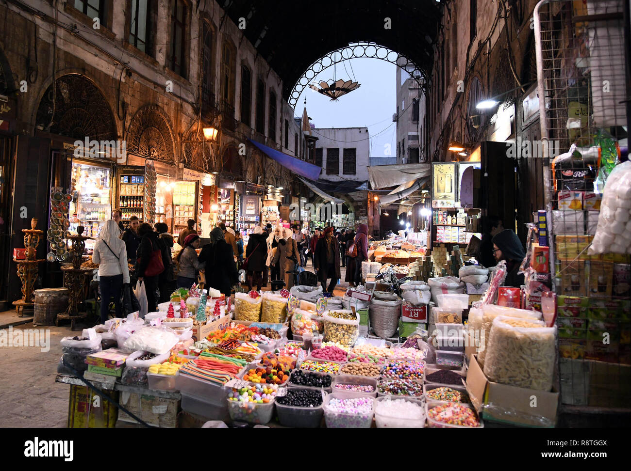 Damascus, Syria. 17th Dec, 2018. People shop at a marketplace in the old city of Damascus, capital of Syria, on Dec. 17, 2018. As Christmas and the New Year approach, Syrians in Damascus shopped for gifts, candies and decorations at marketplaces. Credit: Ammar Safarjalani/Xinhua/Alamy Live News - Stock Image