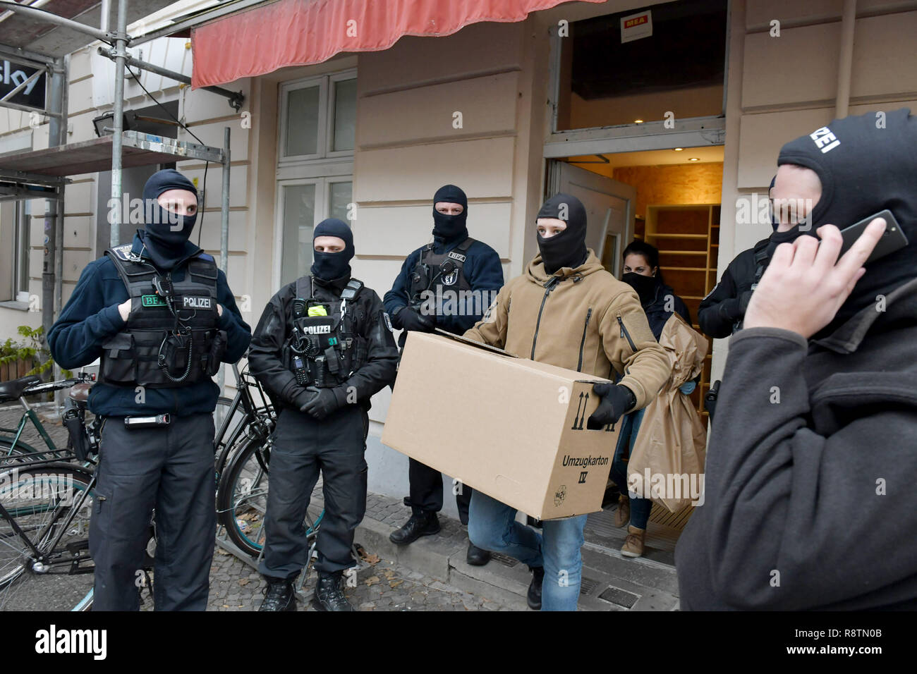 Berlin, Germany. 18th Dec, 2018. Policemen leave a mosque with a cardboard box. In Berlin, investigators search rooms of a mosque and other objects. This concerns the suspicion of terrorist financing. Credit: Paul Zinken/dpa/Alamy Live News - Stock Image