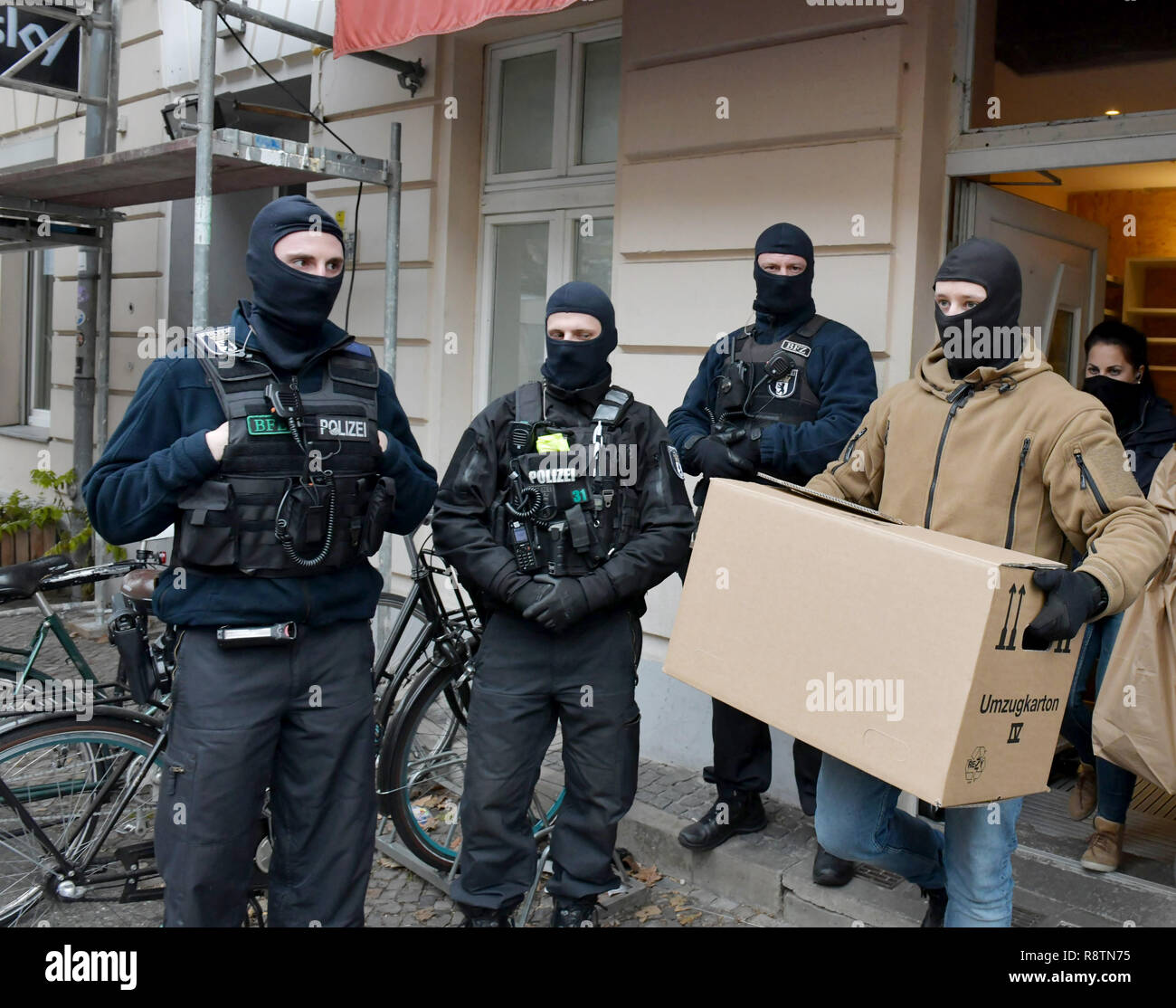 Berlin, Germany. 18th Dec, 2018. Policemen leave a mosque with a cardboard box. In Berlin, investigators search rooms of a mosque and other objects. This concerns the suspicion of terrorist financing. Credit: Paul Zinken/dpa/Alamy Live News Stock Photo