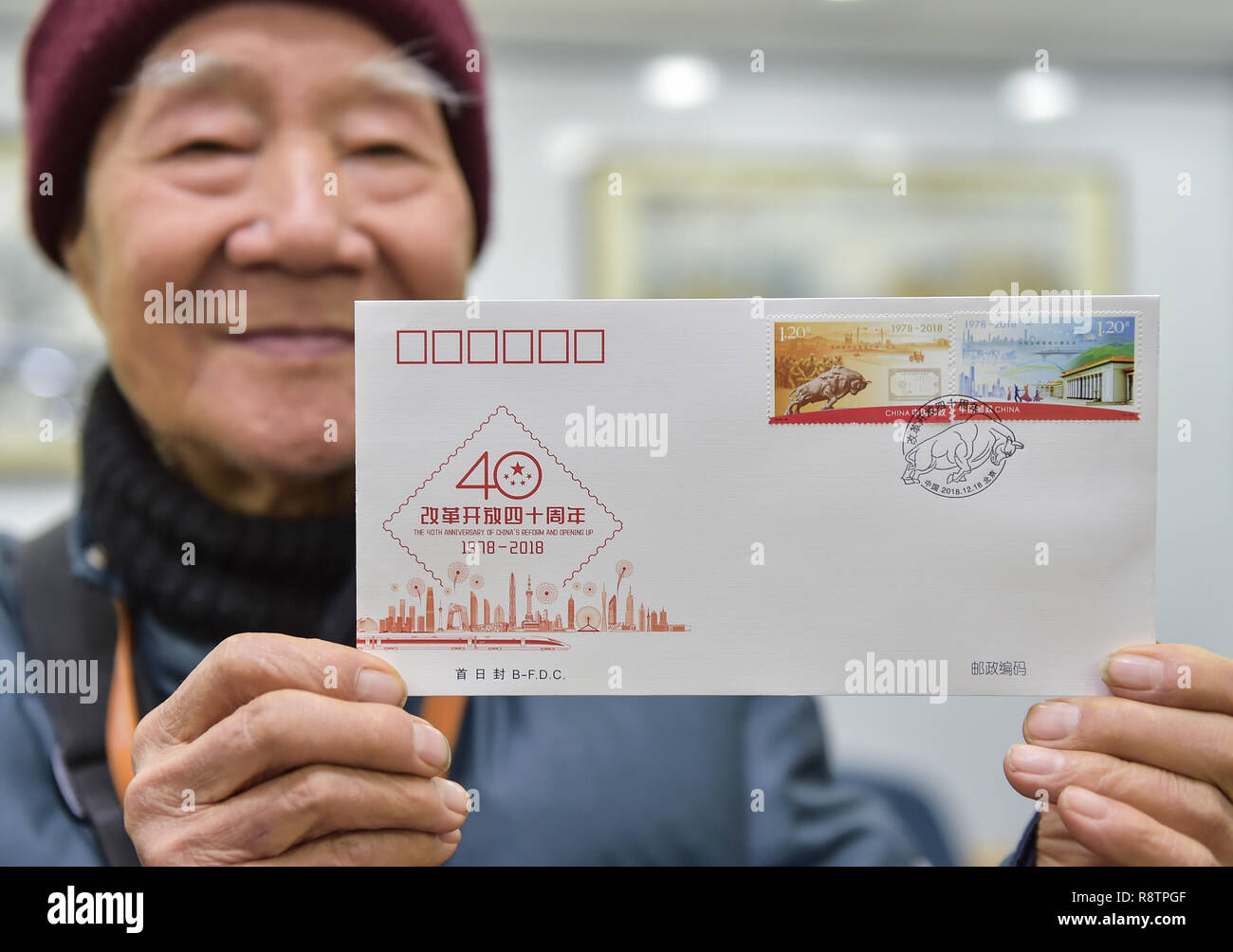 Beijing, China. 18th Dec, 2018. Chang Rongguang, an 82-year-old stamp collector, shows the first day cover with stamps released to mark the 40th anniversary of China's reform and opening up at a post office in Xicheng District of Beijing, capital of China, Dec. 18, 2018. China Post released a set of commemorative stamps and one souvenir sheet marking the 40th anniversary of China's reform and opening up on Tuesday. Credit: Li He/Xinhua/Alamy Live News - Stock Image