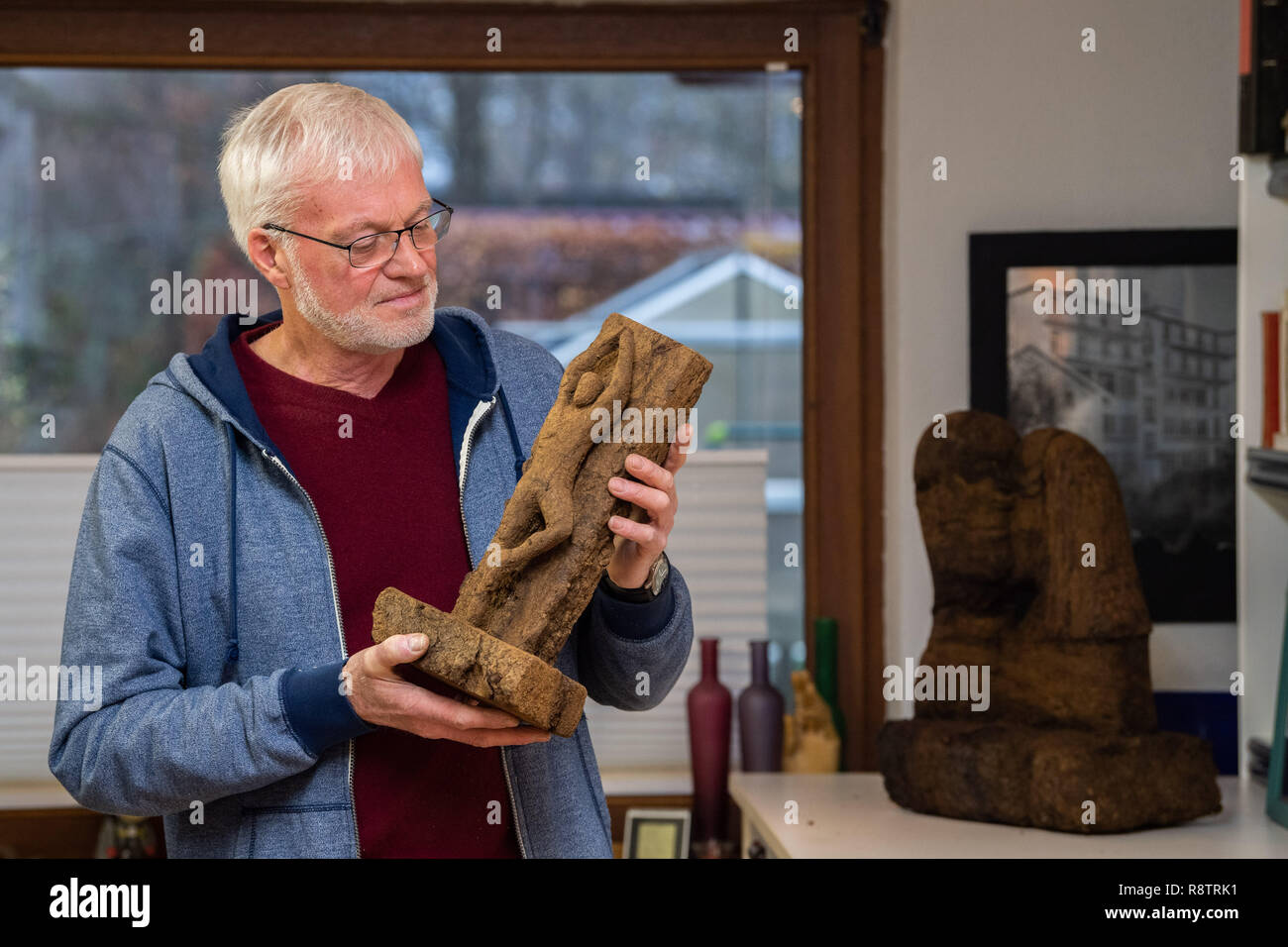 Saterland, Germany. 22nd Nov, 2018. Karl-Heinz Brinkmann holds the figure 'The Dancer' carved from peat in his hands in his home workshop. The 64 year old Saterland artist works with many materials. But the dried white peat is special: it is 2000 years old. Credit: Mohssen Assanimoghaddam/dpa/Alamy Live News - Stock Image