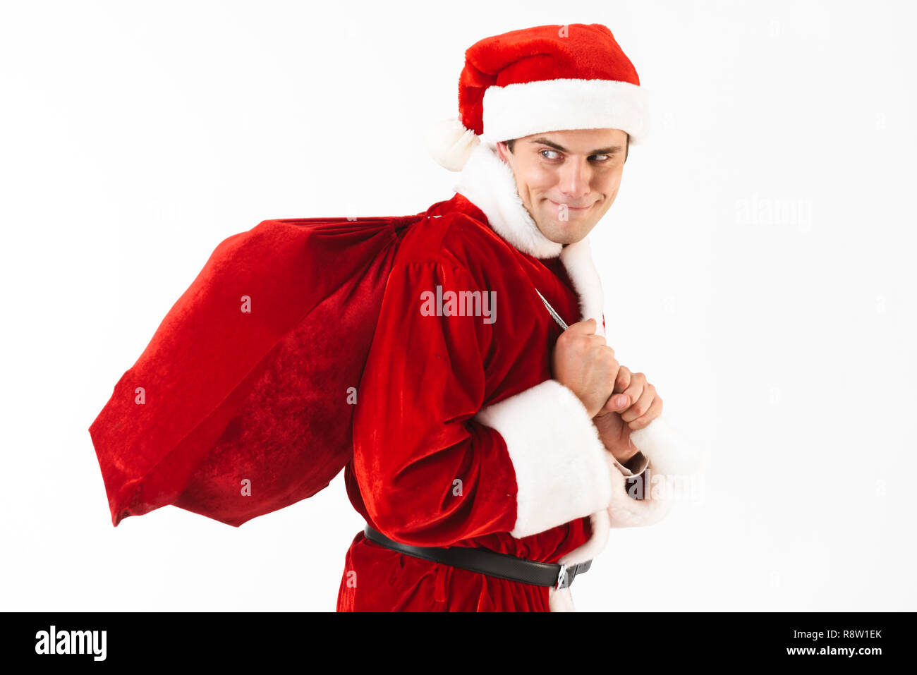 Portrait of tricky man 30s in santa claus costume and red hat walking with gift bag over shoulder isolated on white background in studio - Stock Image