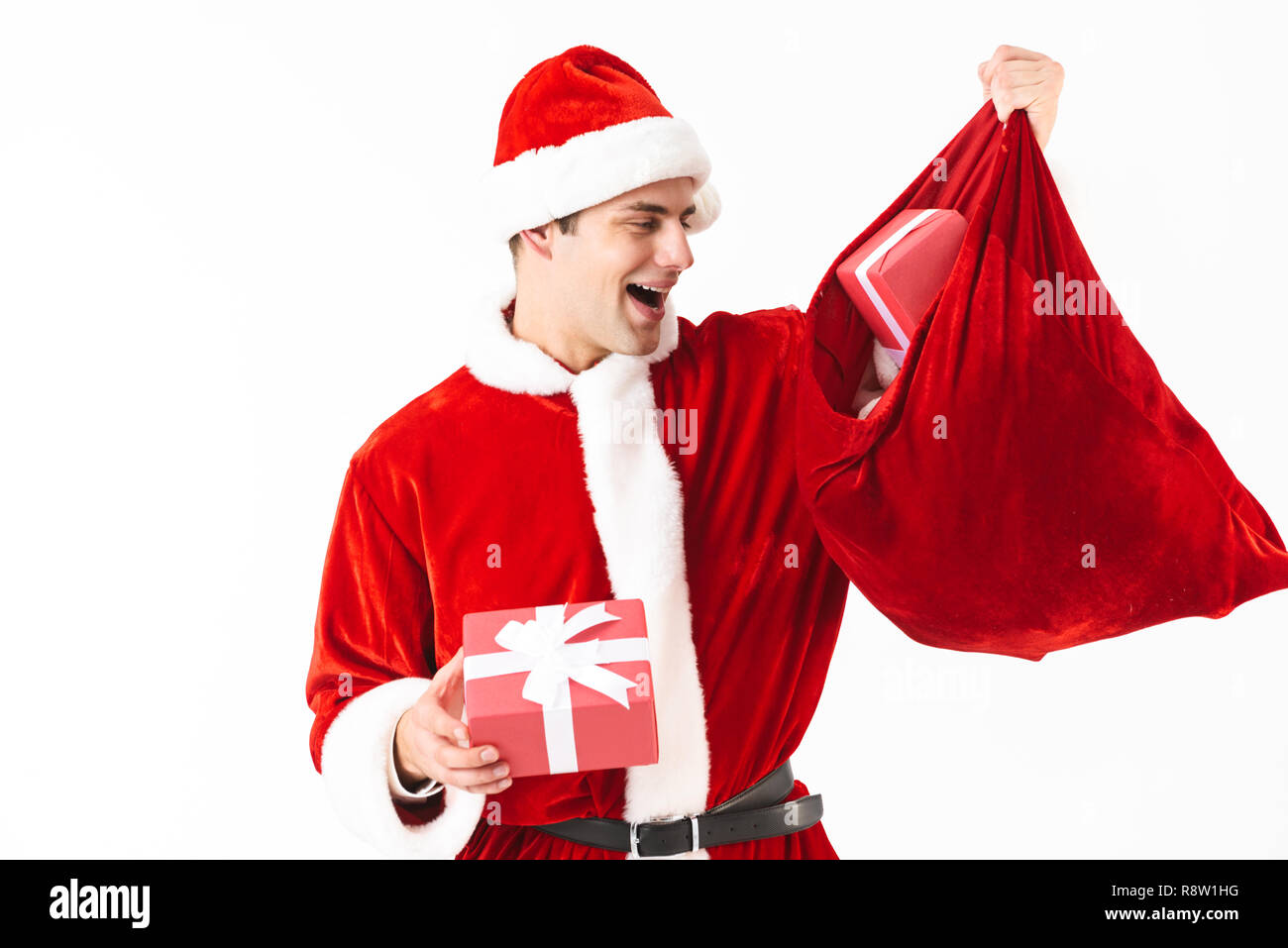 Portrait of generous man 30s in santa claus costume and red hat holding festive bag with gift boxes isolated on white background in studio - Stock Image