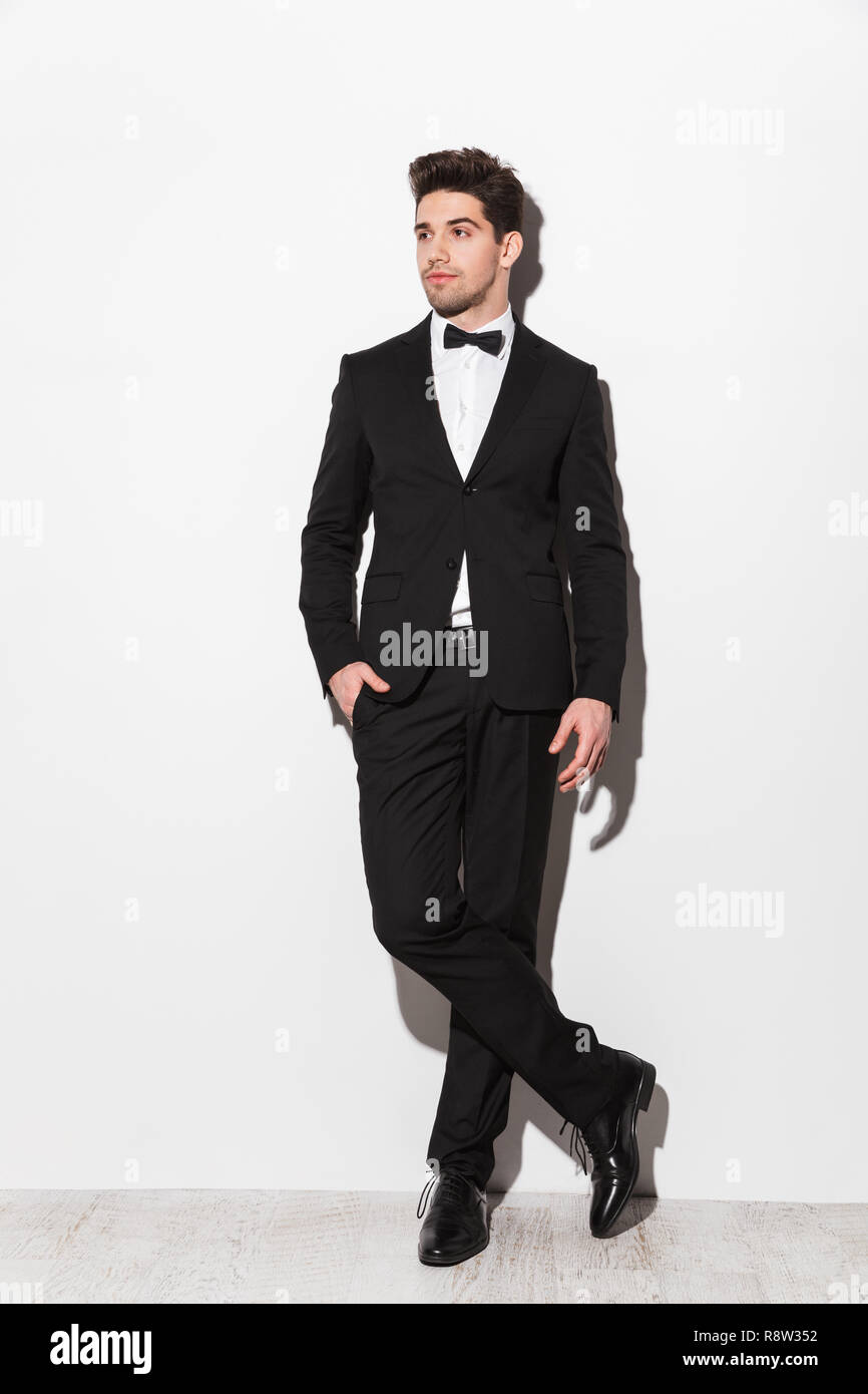 f27ded70ee Full length portrait of a handsome young man wearing black suit with a bow  standing isolated over white background, posing