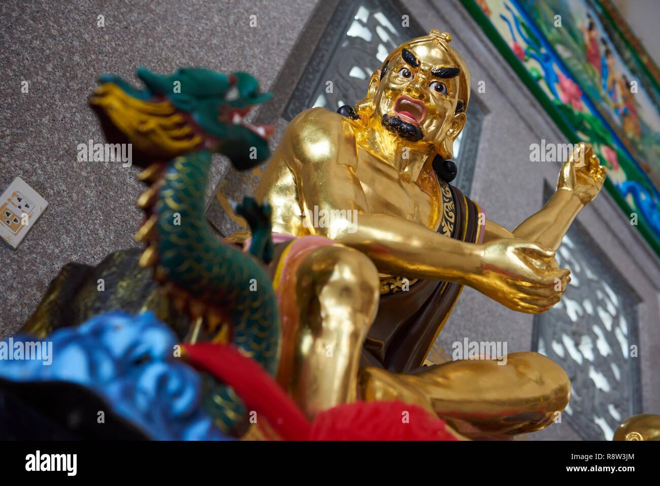 Detail of Gilt Lohan Arhat taming a dragon, inside Kuang Im Chapel, near River Kwai, Kanchanaburi, Thailand. Stock Photo