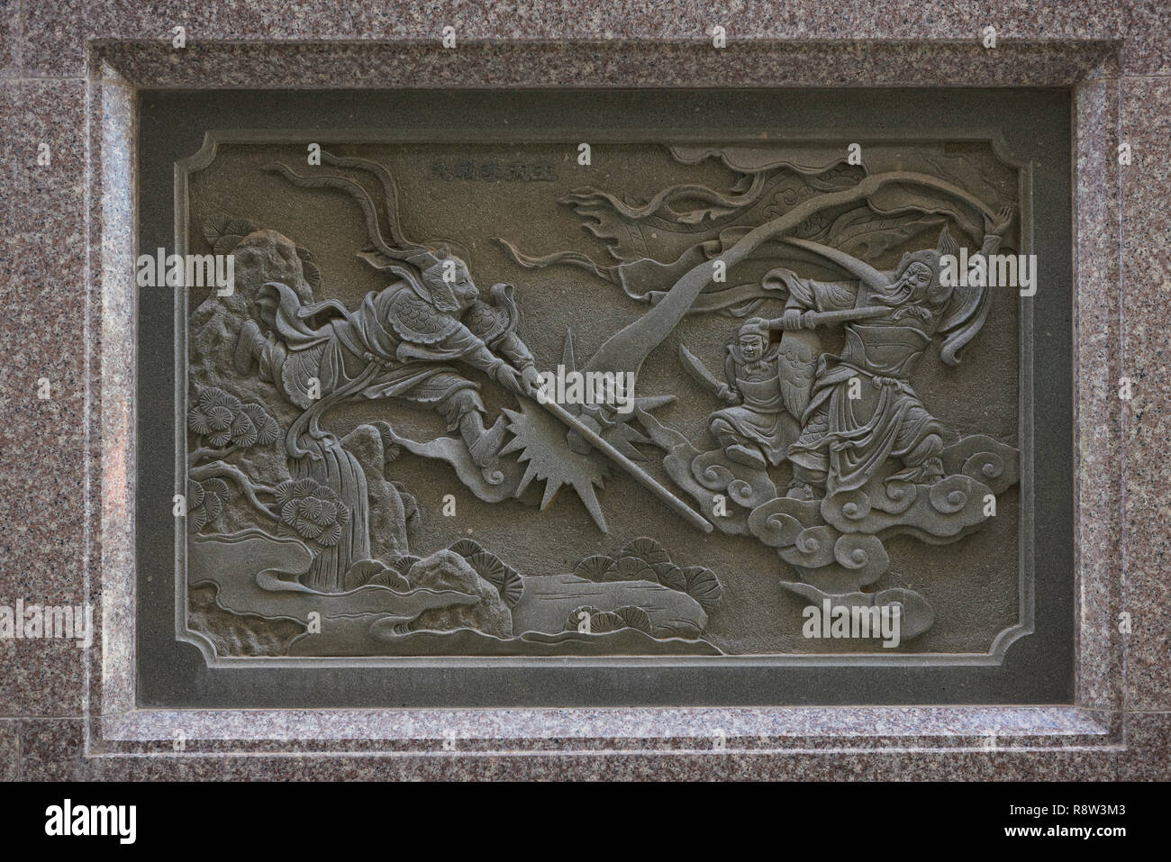 Detail of stone carving at the back of Kuang Im Chapel, near River Kwai, Kanchanaburi, Thailand. The artwork depicts Sun Wukong, or Monkey King, fight Stock Photo