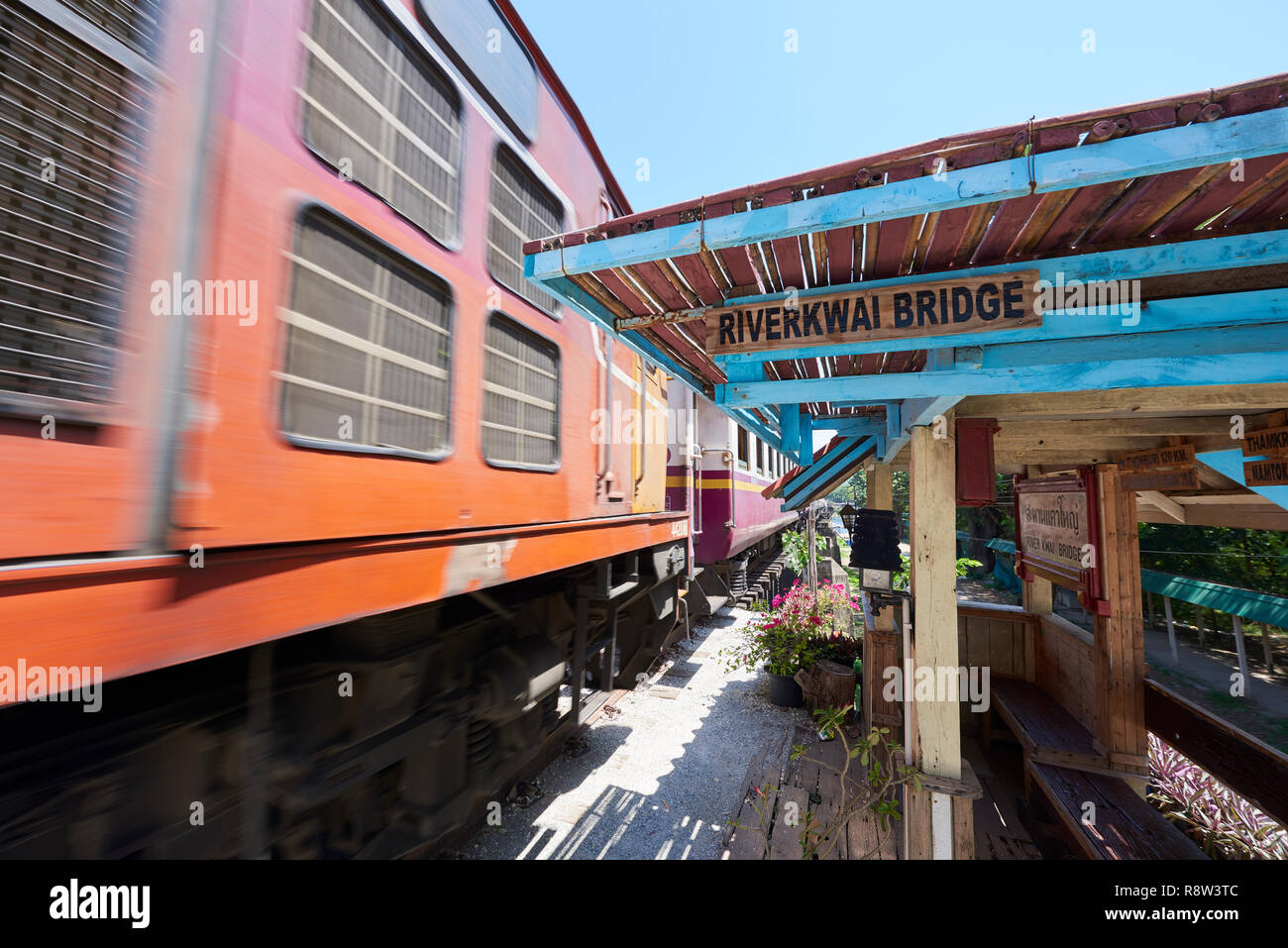 Motion-blurred train whizzes past old waiting gazibo of the Siam-Burma Railway over River Kwai in Kanchanaburi, Thailand. The infamous River Kwai brid Stock Photo