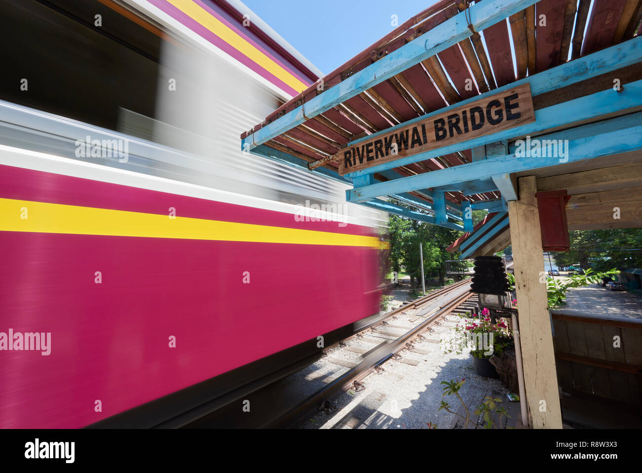Motion-blurred train whizzes past old waiting gazibo of the Siam-Burma Railway over River Kwai in Kanchanaburi, Thailand. The infamous River Kwai brid Stock Photo