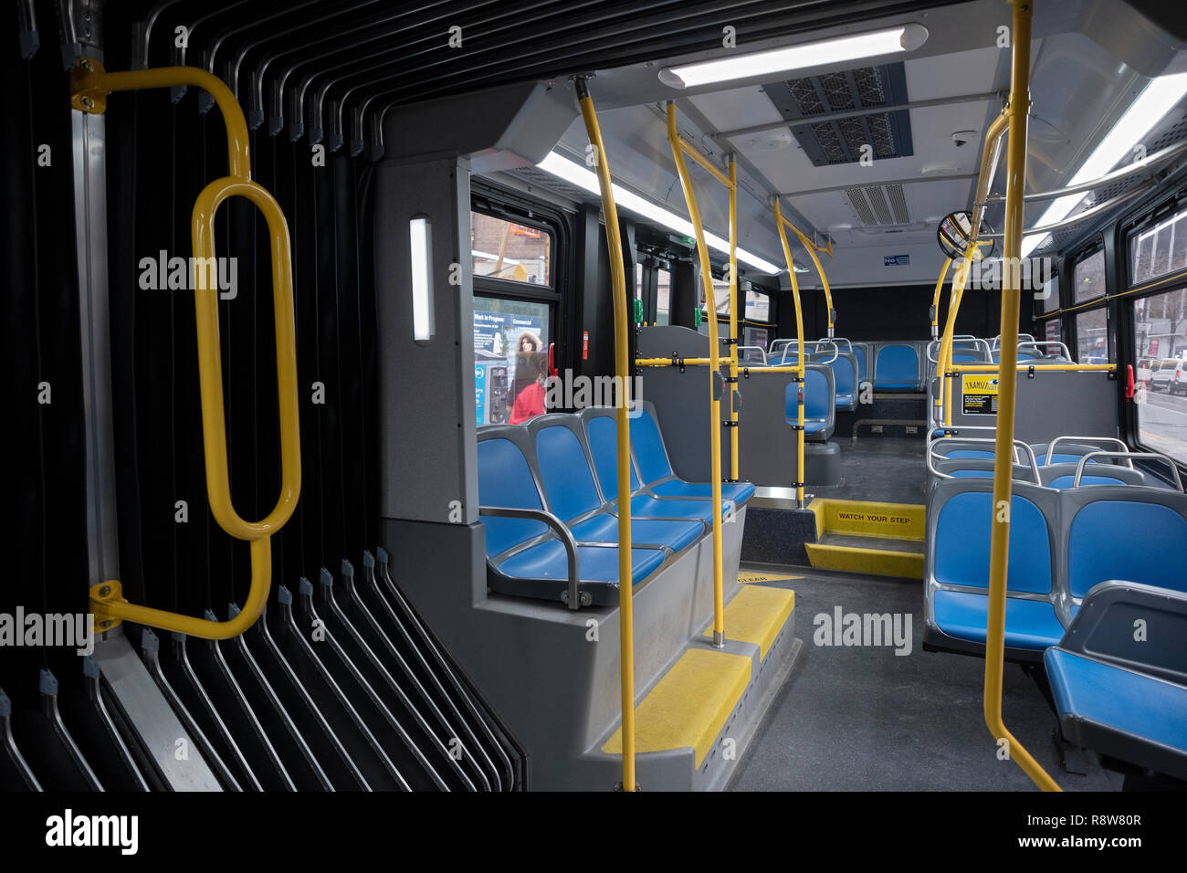 the interior rear of one of New York City's new articulated accordion buses traveling west on 34th Street in Midtown Manhattan. - Stock Image