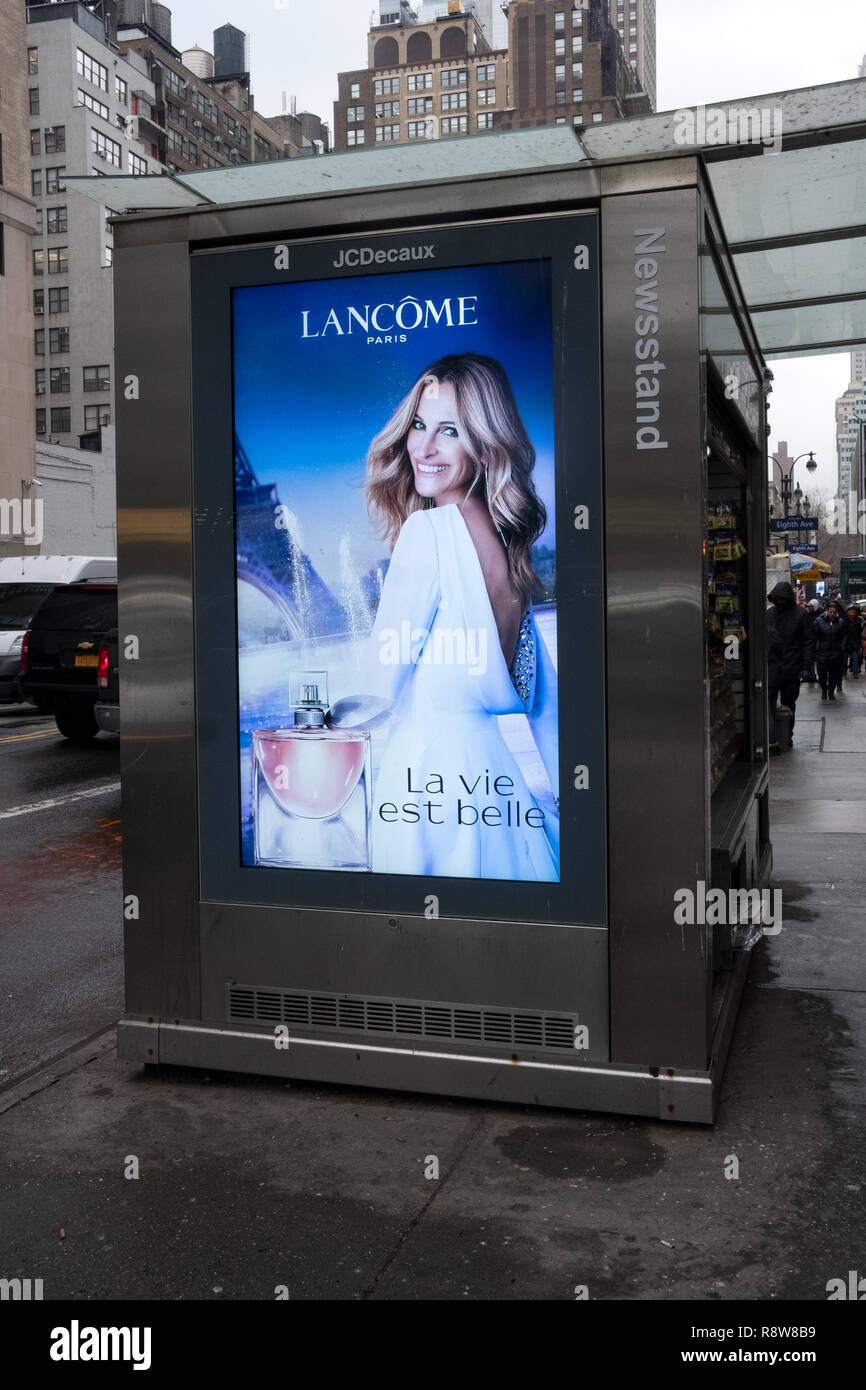 An advertisement on the side of a newsstand featuring Julia Roberts promoting Lancome perfume. - Stock Image