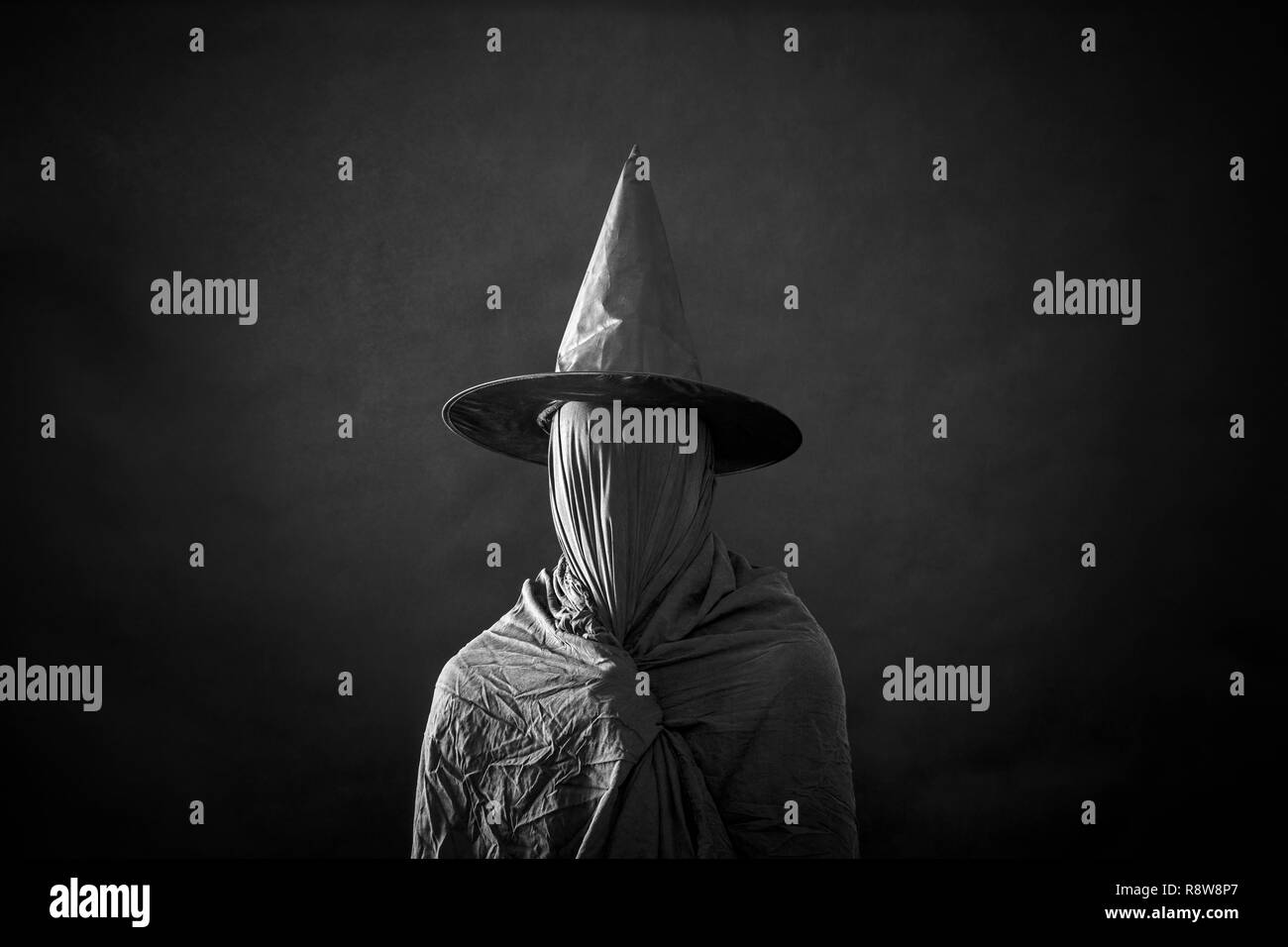 Ghostly figure with long hat in the dark - Stock Image