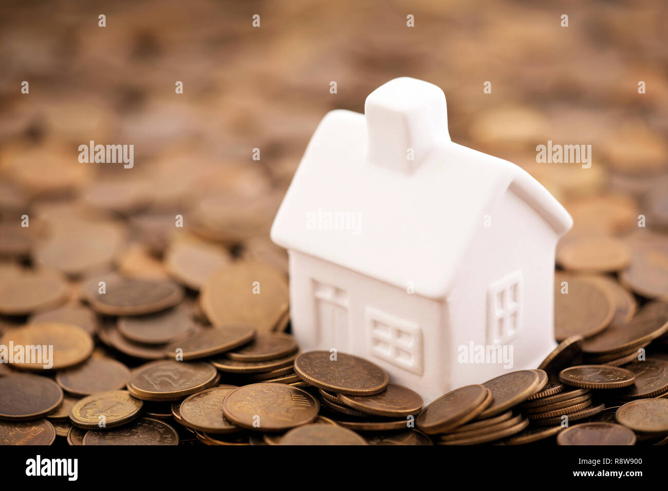 Small toy house on coins - Stock Image