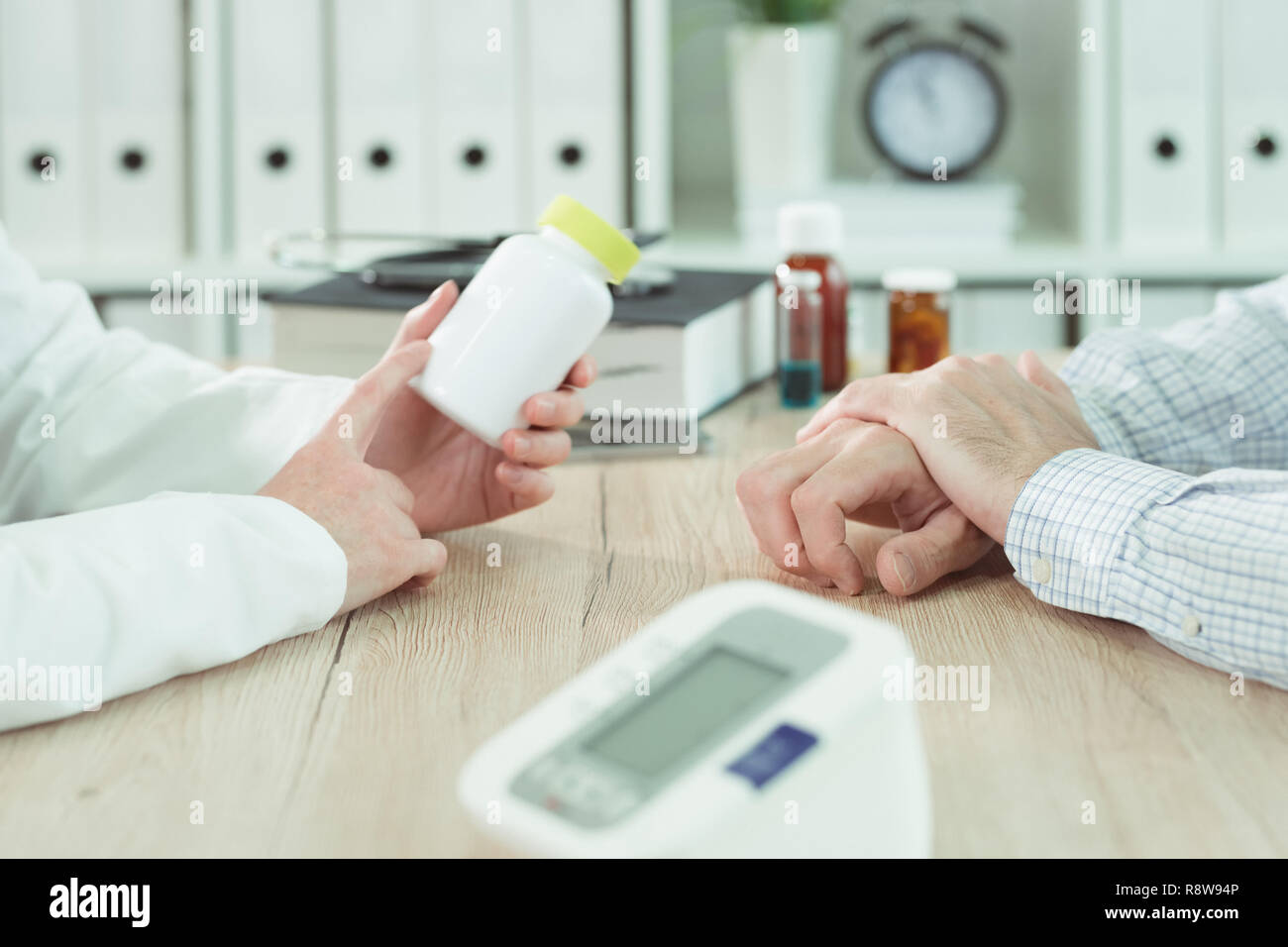 Doctor and patient considering nutritional supplement therapy in medical office - Stock Image