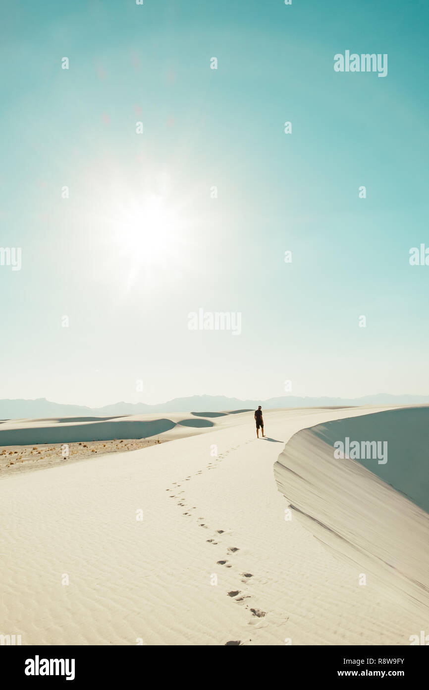 A man walking the sand dunes of White Sands National Monument in New Mexico, USA - Stock Image