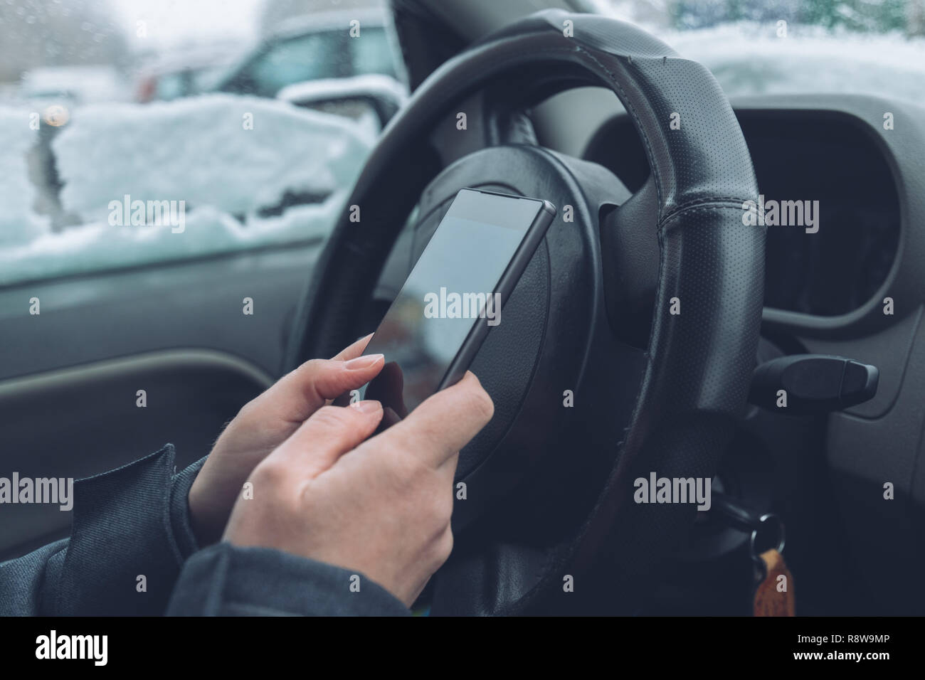 Texting in parked car while the snow is falling outside, close up of hands typing message on mobile phone, selective focus - Stock Image