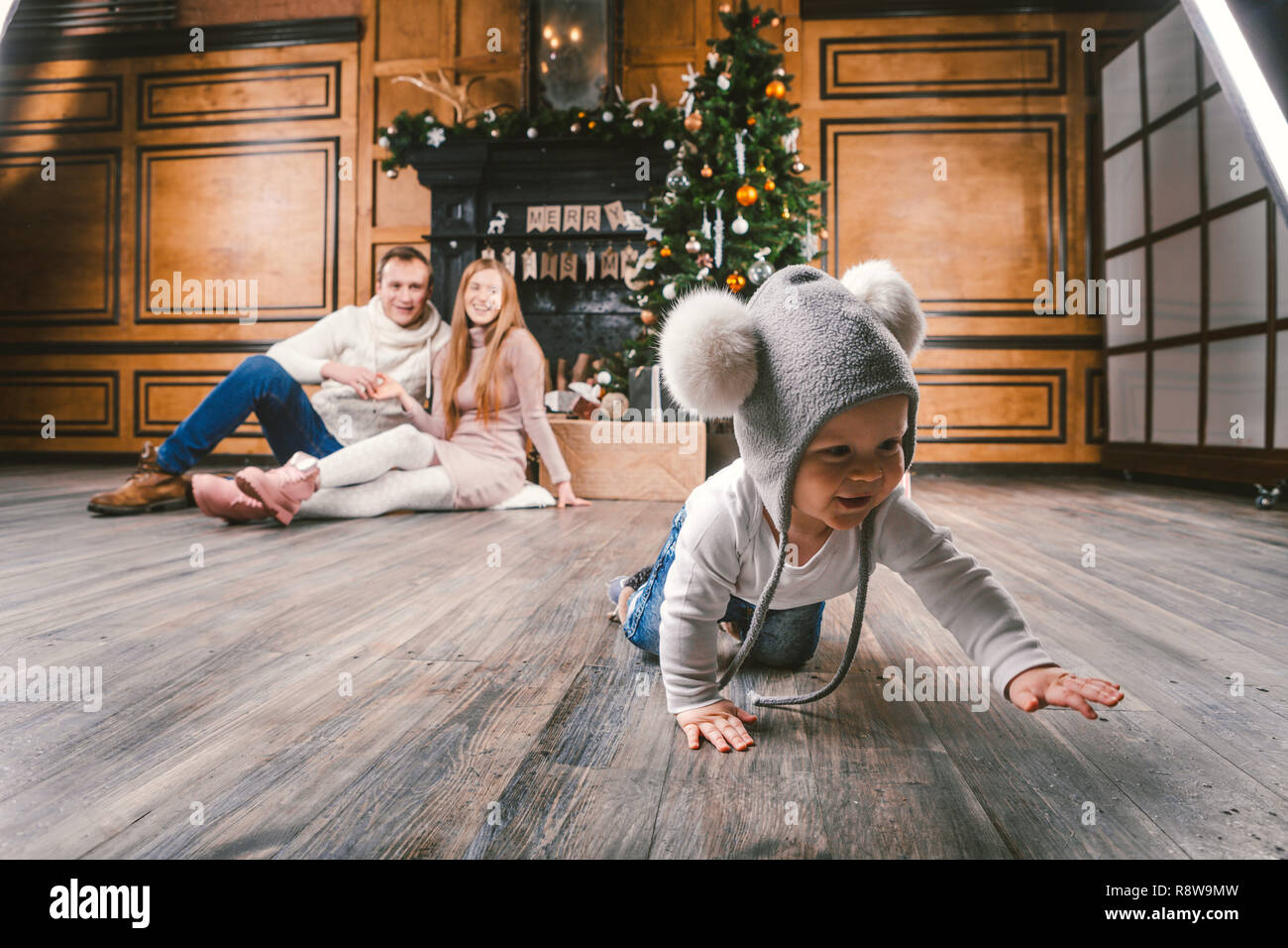 theme family holiday New Year and Christmas. Young caucasian family mom dad son 1 year sit wooden floor near fireplace christmas tree on Christmas eve - Stock Image