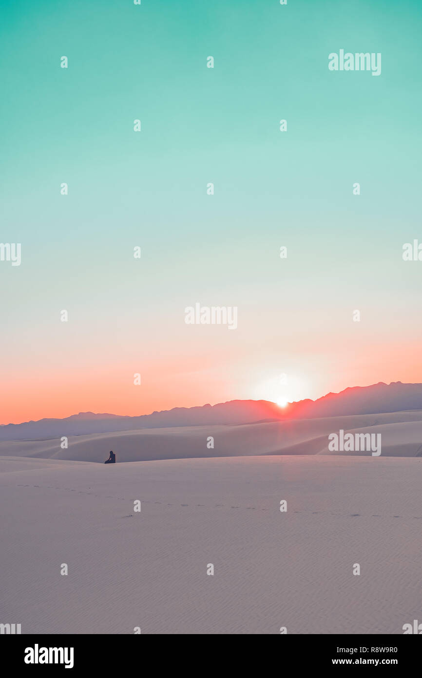 A girl watching a dramatic sunset in White Sands National Monument in New Mexico, USA - Stock Image