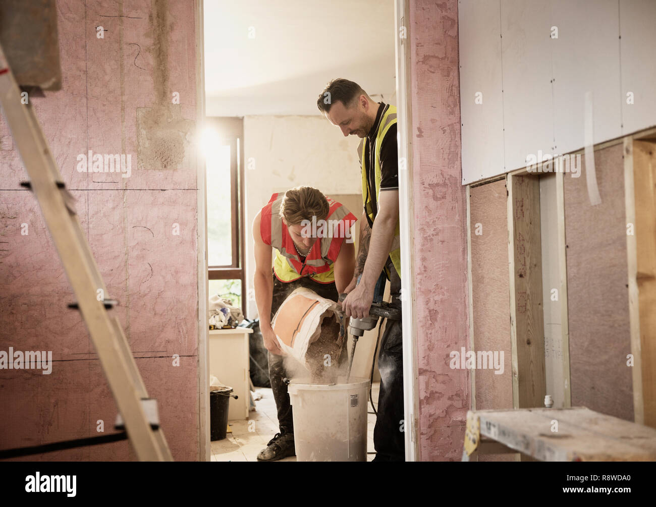 Construction workers mixing plaster in house Stock Photo