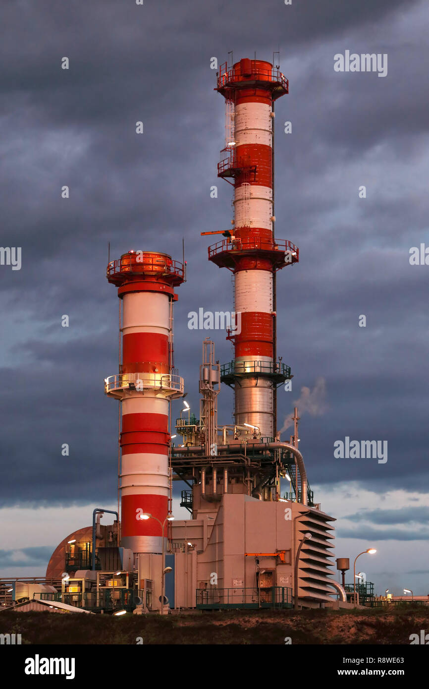 Part of a big oil refinery and powerplant at dusk - Stock Image
