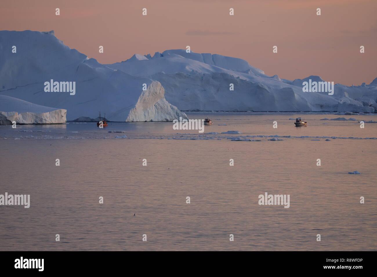 Ilulissat Eisberge am Abend Lichtkunst vom Feinsten. Kleine Ausflugsboote bringen die Touristen direkt an die weißen Riesen - Stock Image