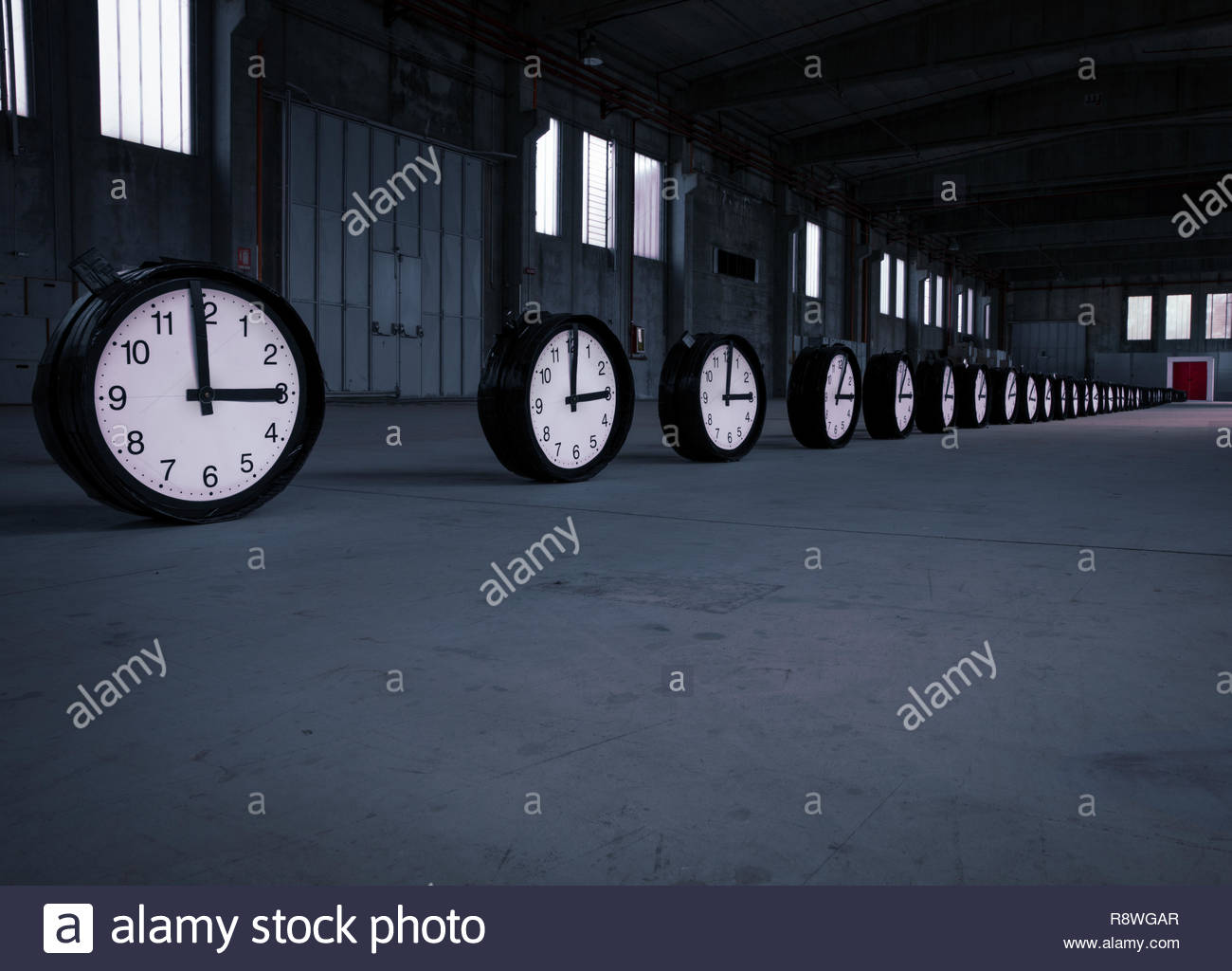 Fifty black clocks with hands on 3 o'clock are placed in a oblique row pointing to a double red door in an empty factory. - Stock Image