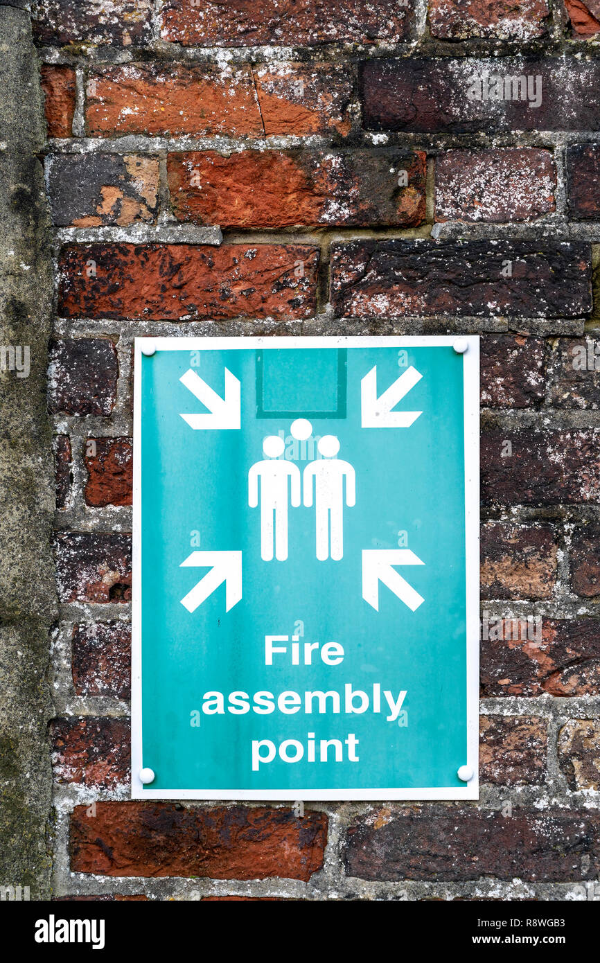 Fire assembly point sign on brick wall - Stock Image