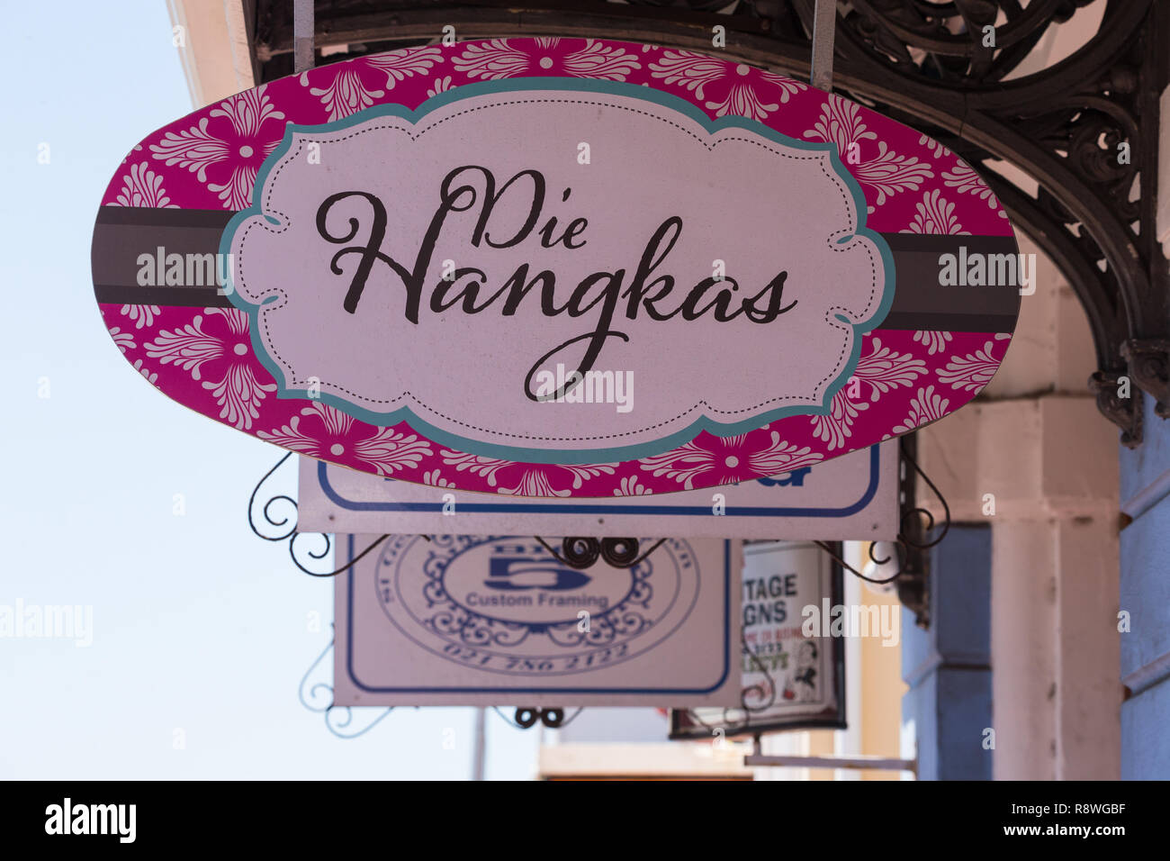 shop signs hanging outside shops on the main road of Simonstown, Cape Peninsula, South Africa - Stock Image