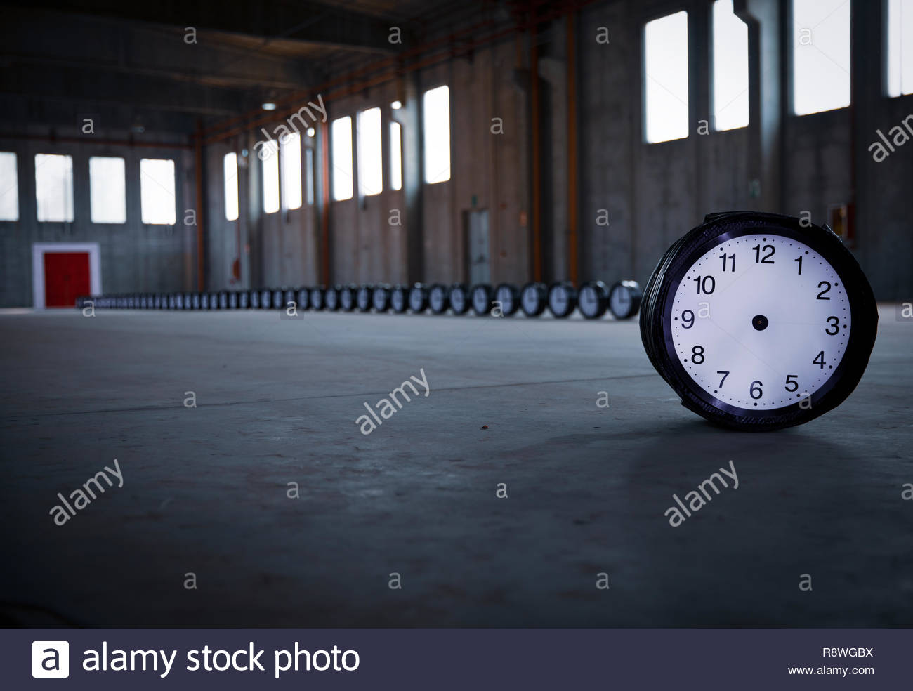 A clock with no hands stands in the foreground, on the right, with 50 clocks behind, settled in a row pointing to a red door in an empty factory. - Stock Image