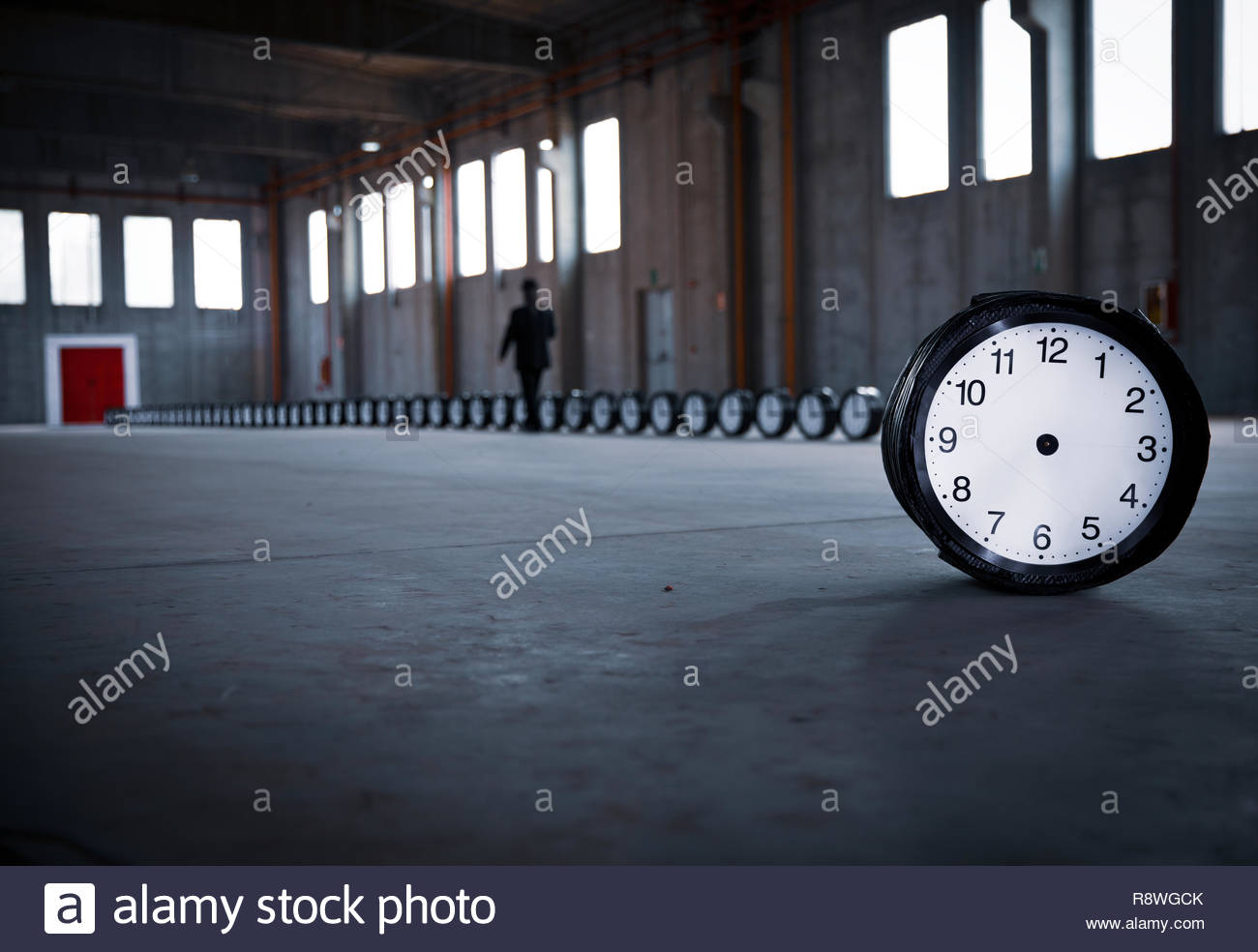 A no-hand clock stands in the foreground, on the right, while a man, dressed in black, is walking alongside a row of 50 clocks in an empty factory. - Stock Image