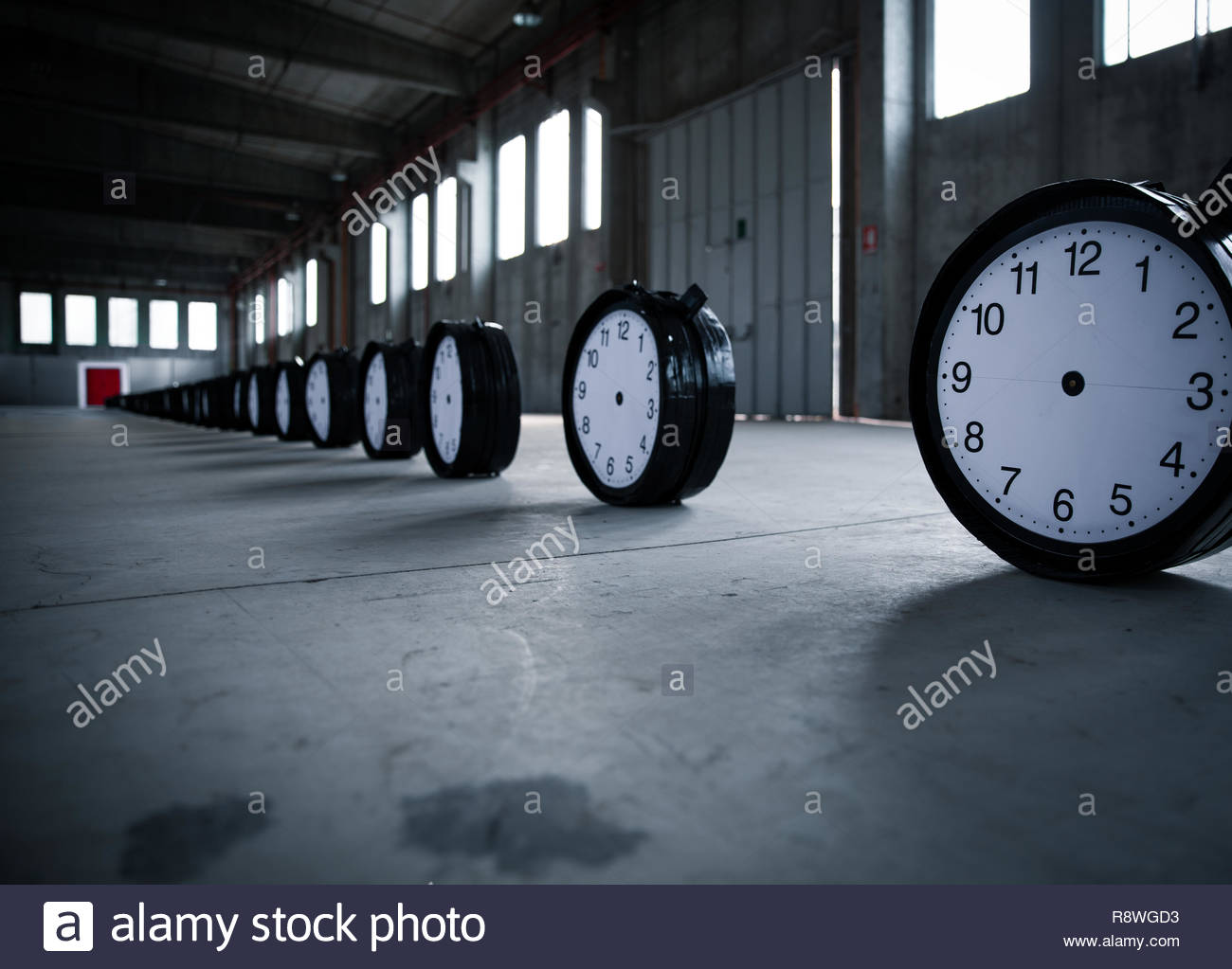 Fifty black clocks are placed in a row pointing to a double red door in an empty factory. - Stock Image
