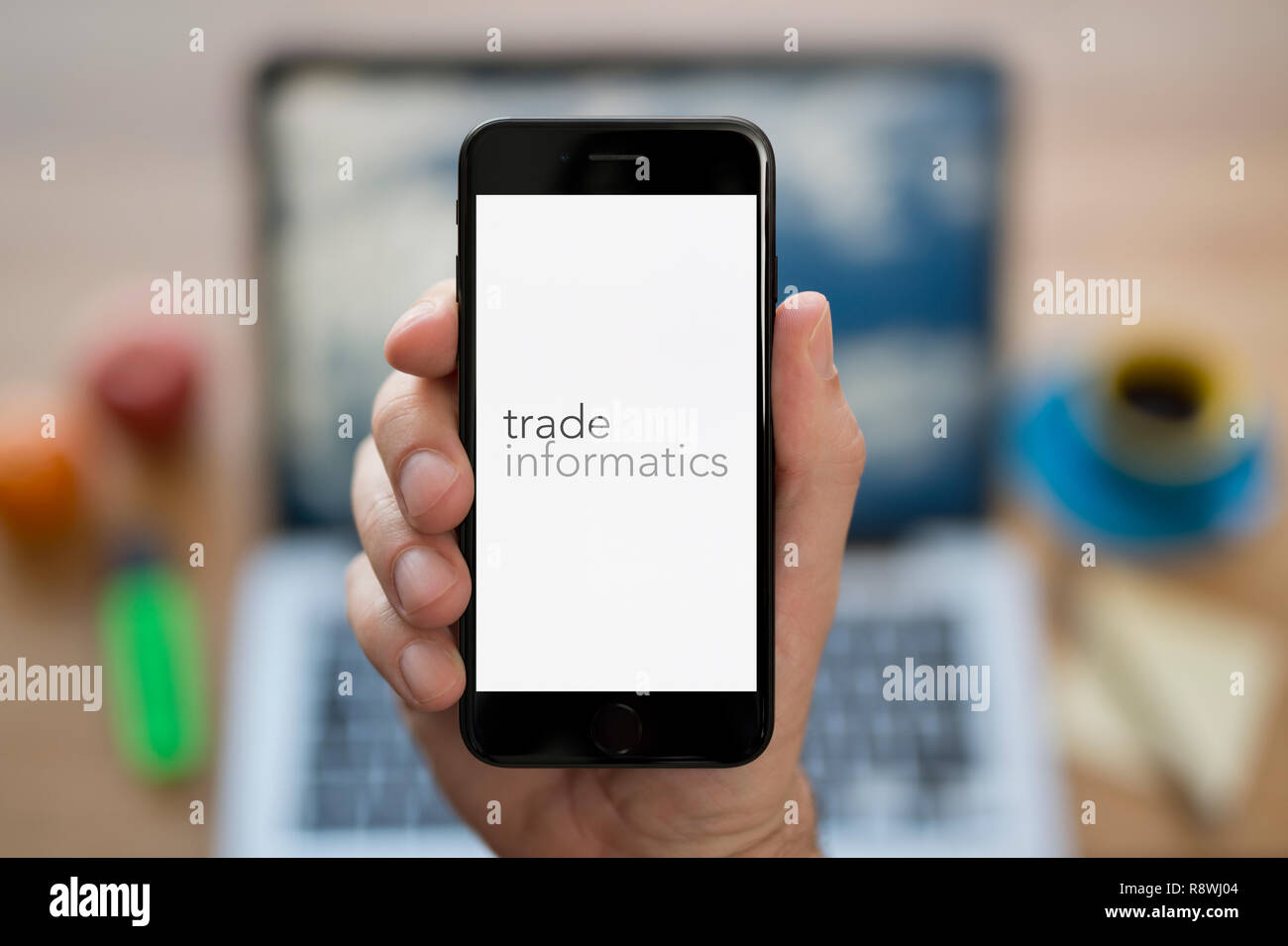 A man looks at his iPhone which displays the Trade Informatics logo (Editorial use only). - Stock Image