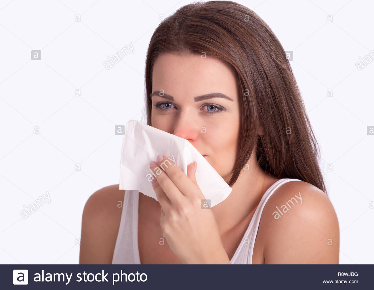 Pretty girl wiping nose with tissue, maybe in flu season - Stock Image