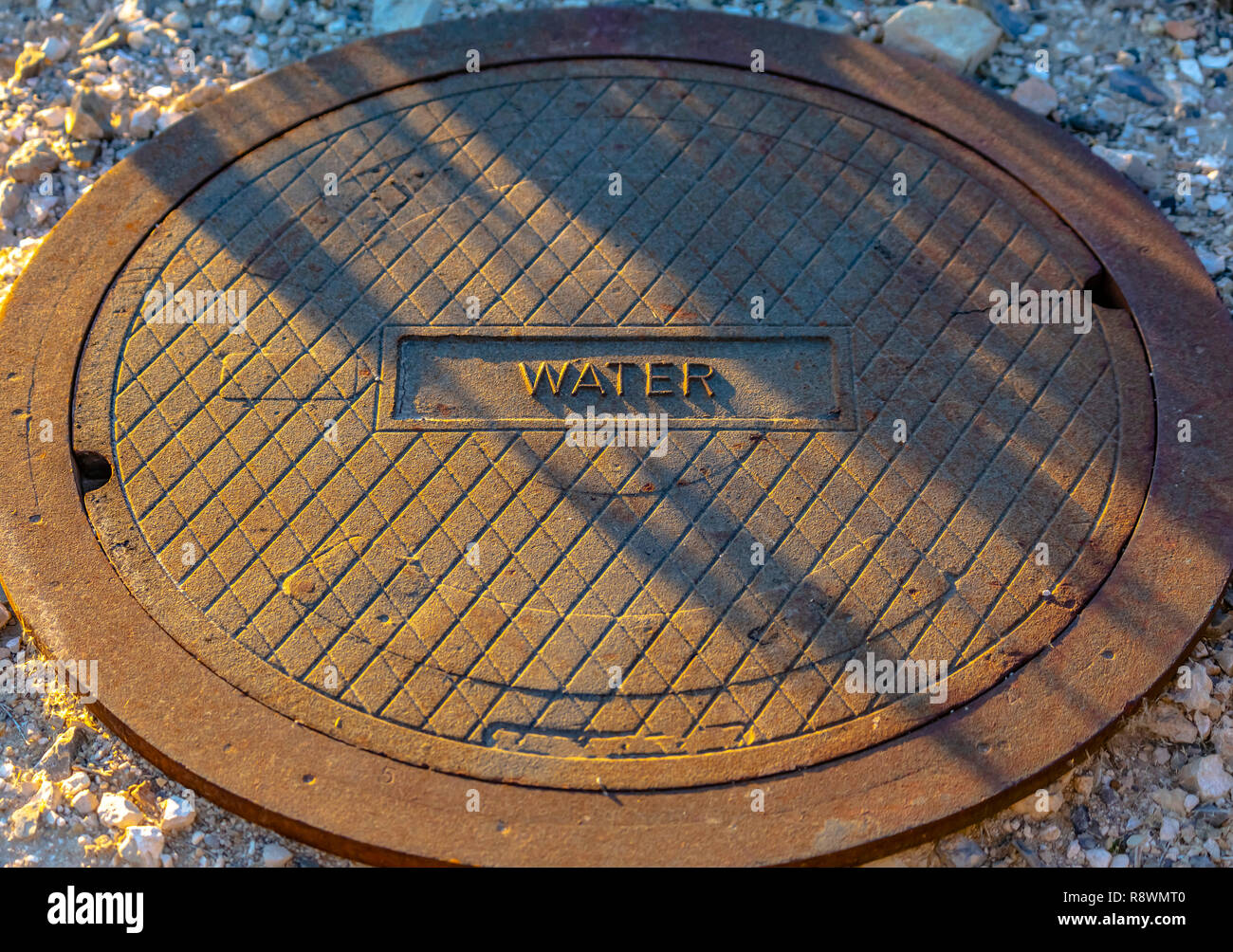 Man hole lid with label of water on the front - Stock Image