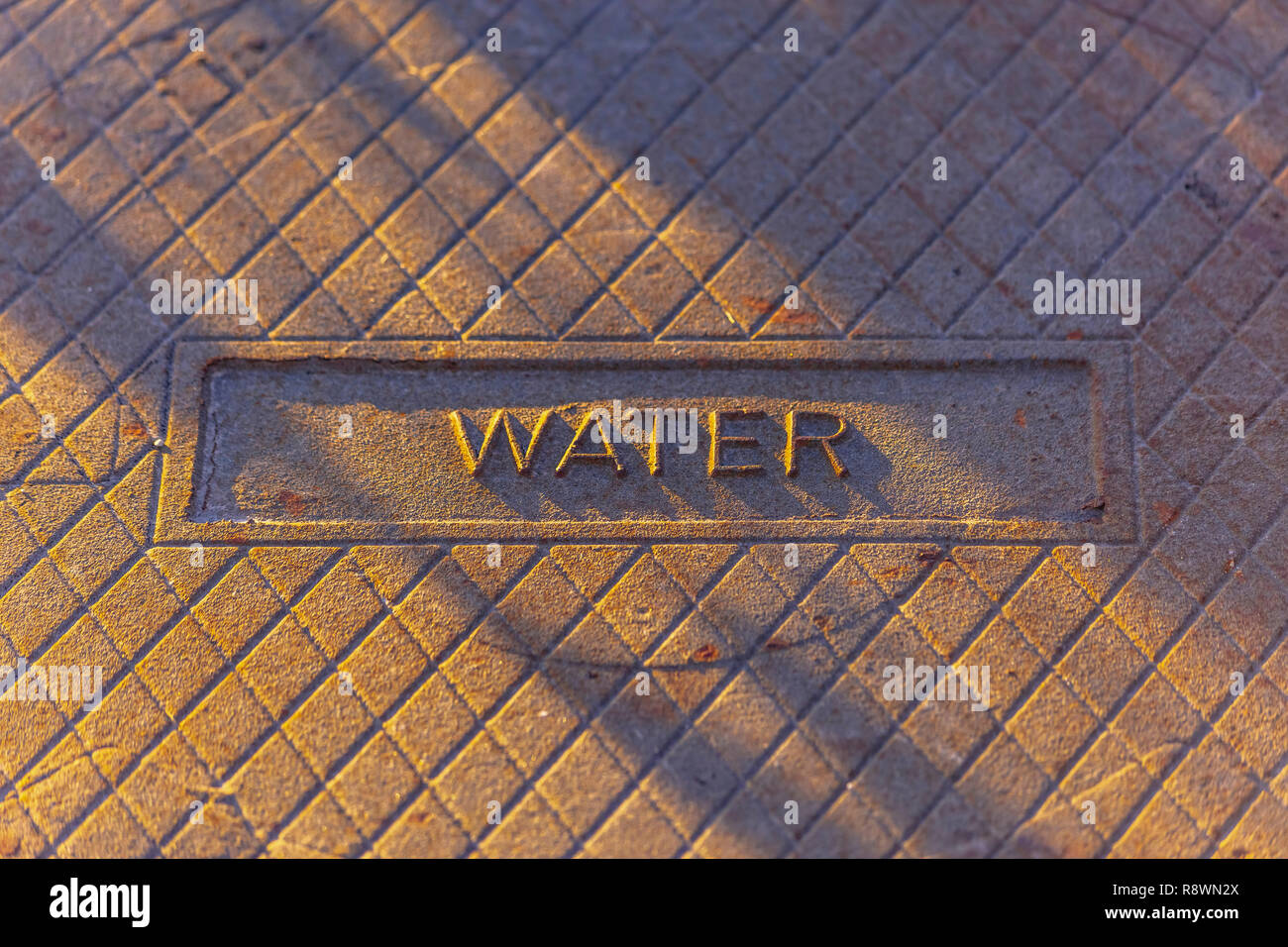 Water stamped on a man hole cover - Stock Image