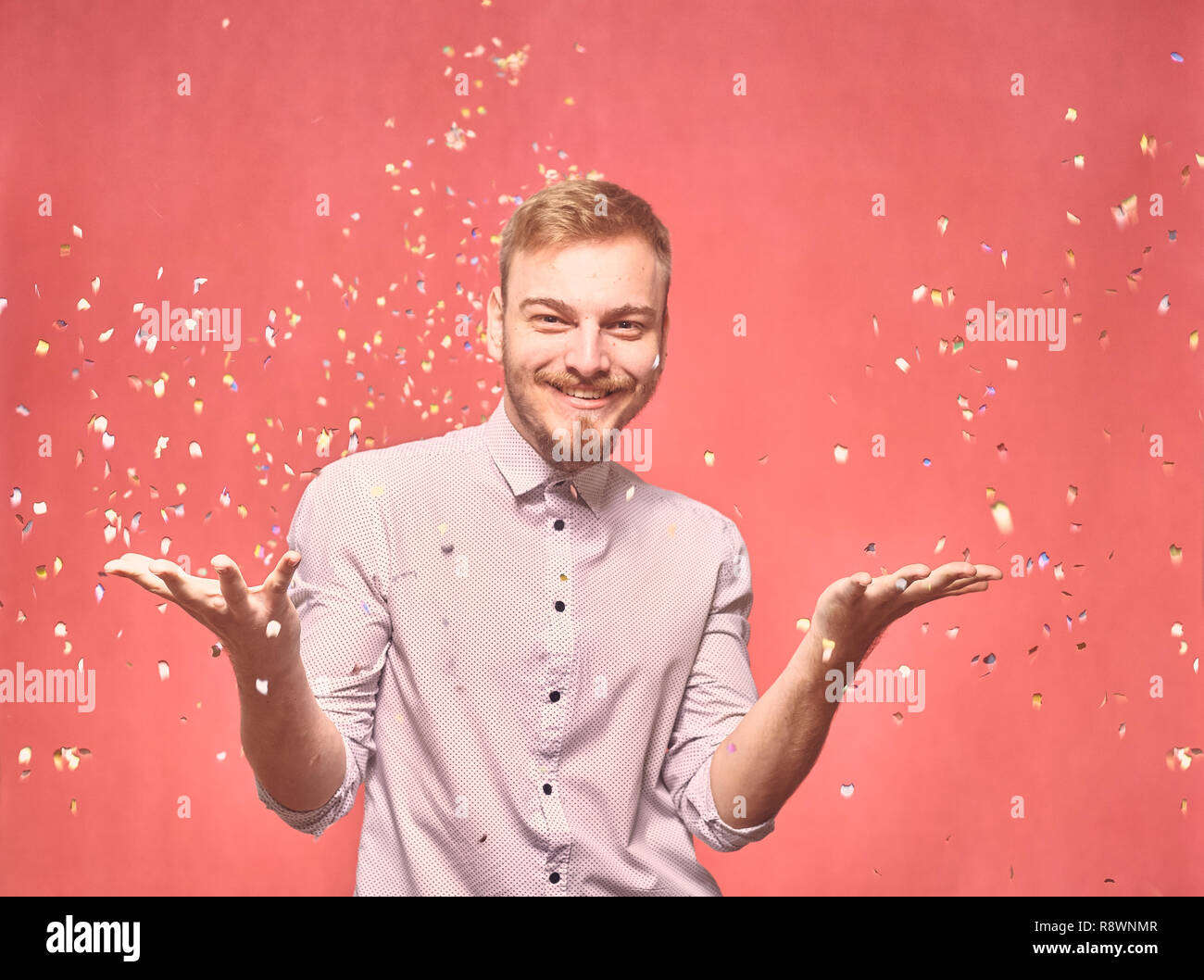 one young man, 20-29 years old, candid smiling happy, throwing confetti flying in air. real person, not model. pink background, studio shot, photo sho - Stock Image