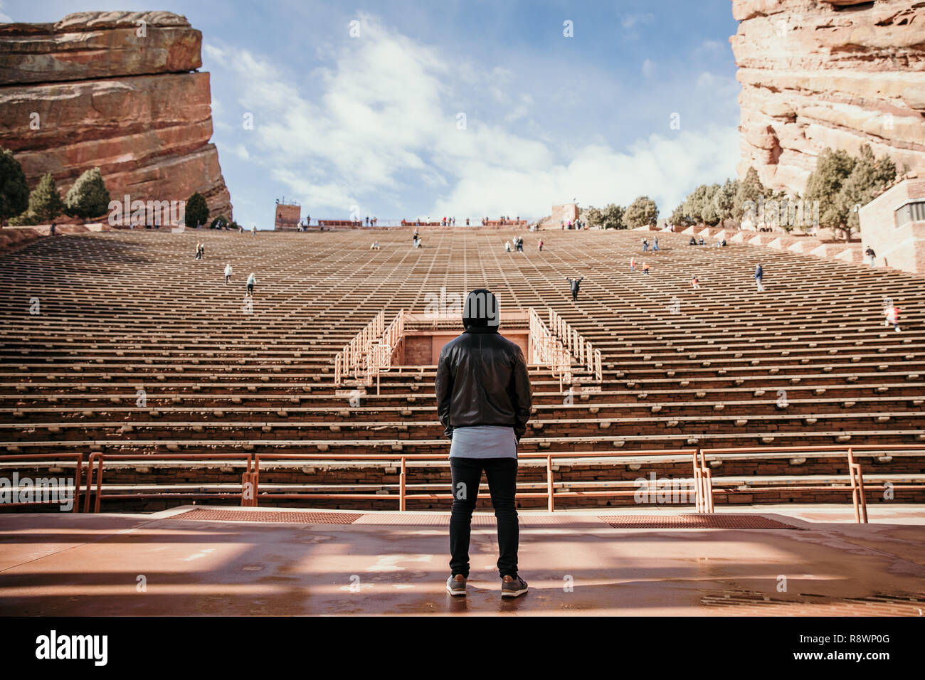 Symmetrical Portrait of Person Standing on a Stage Dreaming while Facing Stadium Stands Seating at Outdoor Amphitheater Concert Music Hall Outside - Stock Image