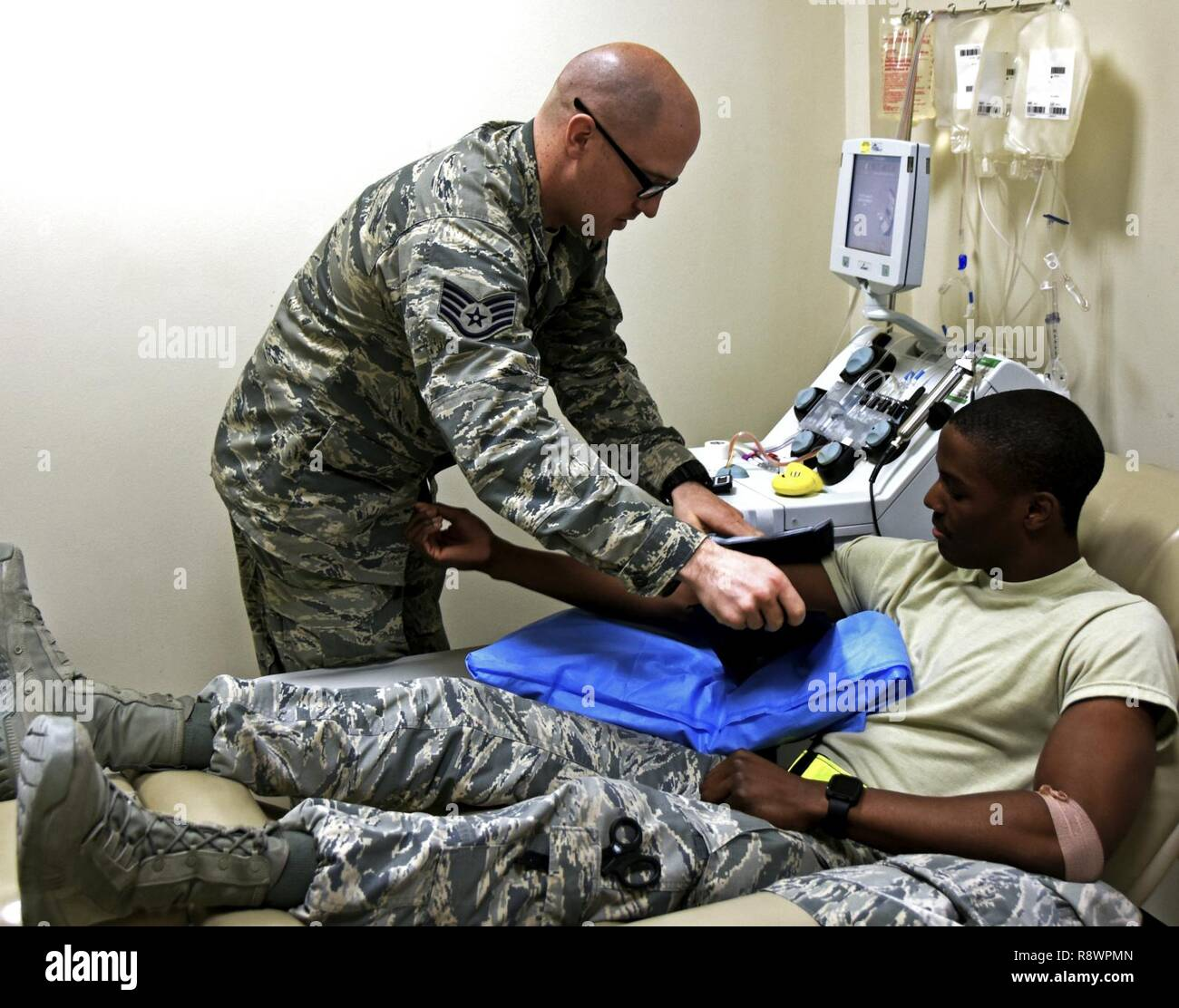 Staff Sgt. Jonathan Flannigan, NCO in charge of the apheresis element with the 379th Expeditionary Medical Group, wraps a pressure cuff around the arm of Senior Airman Jordan Marshall, an aerospace medical technician with the 379th EMDG, at Al Udeid Air Base, Qatar, March 7, 2017. Marshall volunteered to donate blood platelets which are essential to Airmen in combat zones without access to immediate medical treatment. - Stock Image