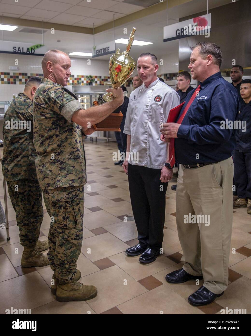 U.S. Marine Corps Col. Scott A. Baldwin, left, assistant chief of staff, Marine Corps Installations Command, presents Master Sgt. Matthew J. Jacobs, regimental mess chief, 2nd Marine Division, with a trophy for the Marine and Mess Attendant Award during an award ceremony for best full food service mess hall in the Marine Corps, Camp Lejeune, N.C., March 14, 2017. The mess halls were judged on factors such as cleanliness, recipe compliance, quality of food, teamwork, execution and training. - Stock Image